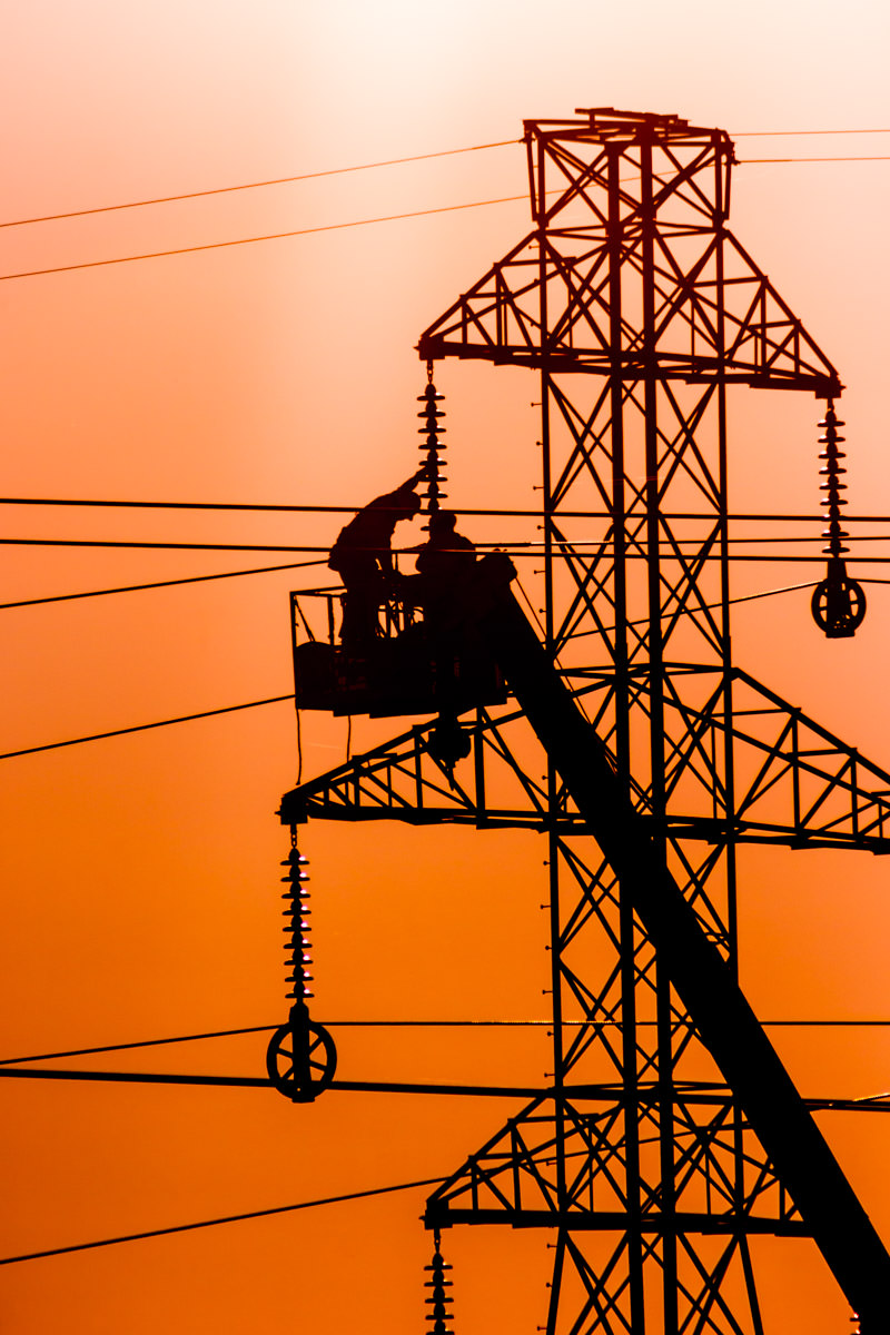 Linemen are silhouetted by the evening sun as they work on a high tension power line's tower in Far North Dallas, Texas.
