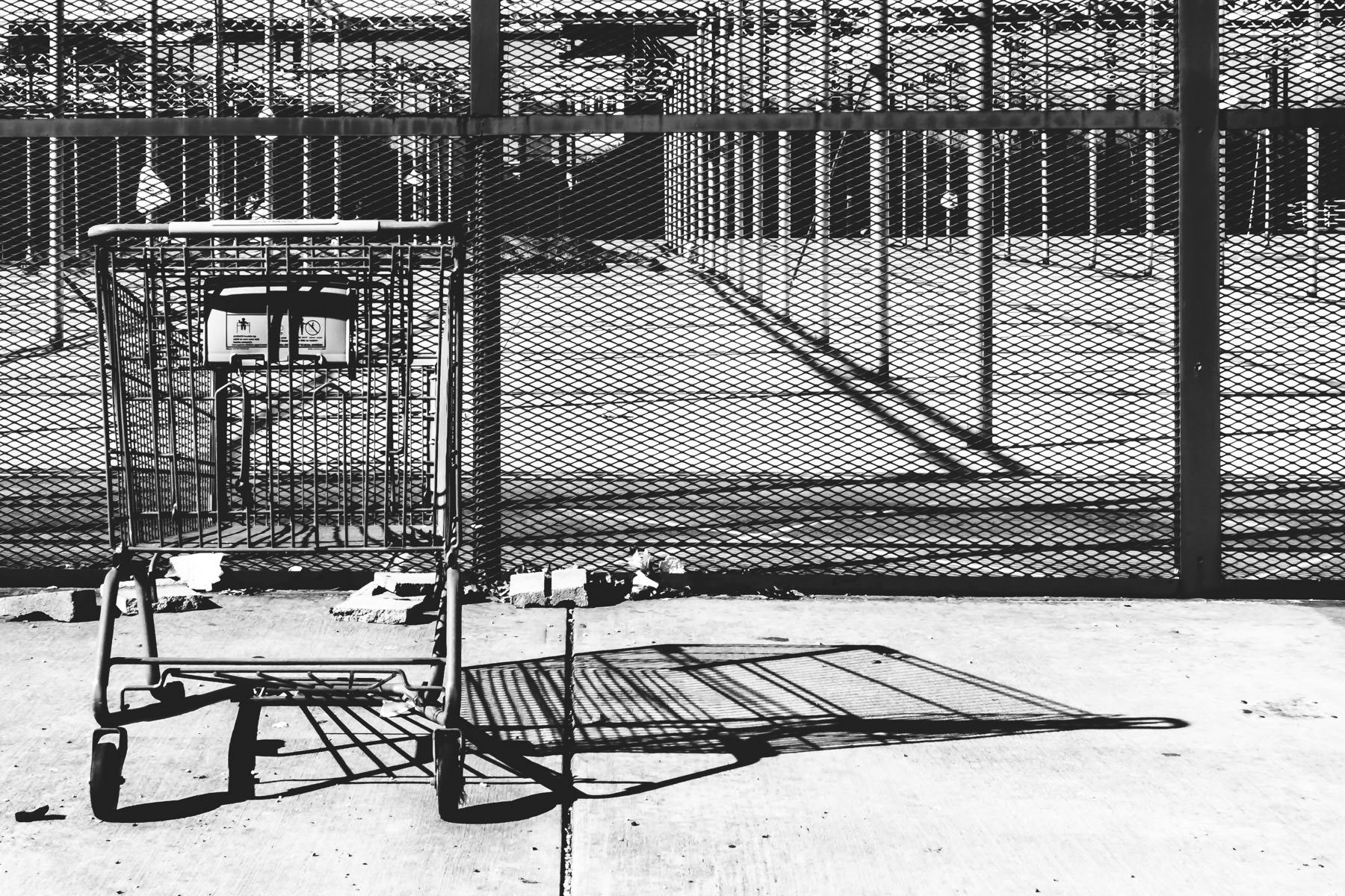 A forlorn shopping cart sits outside the garden center of an abandoned Walmart in Richardson, Texas.