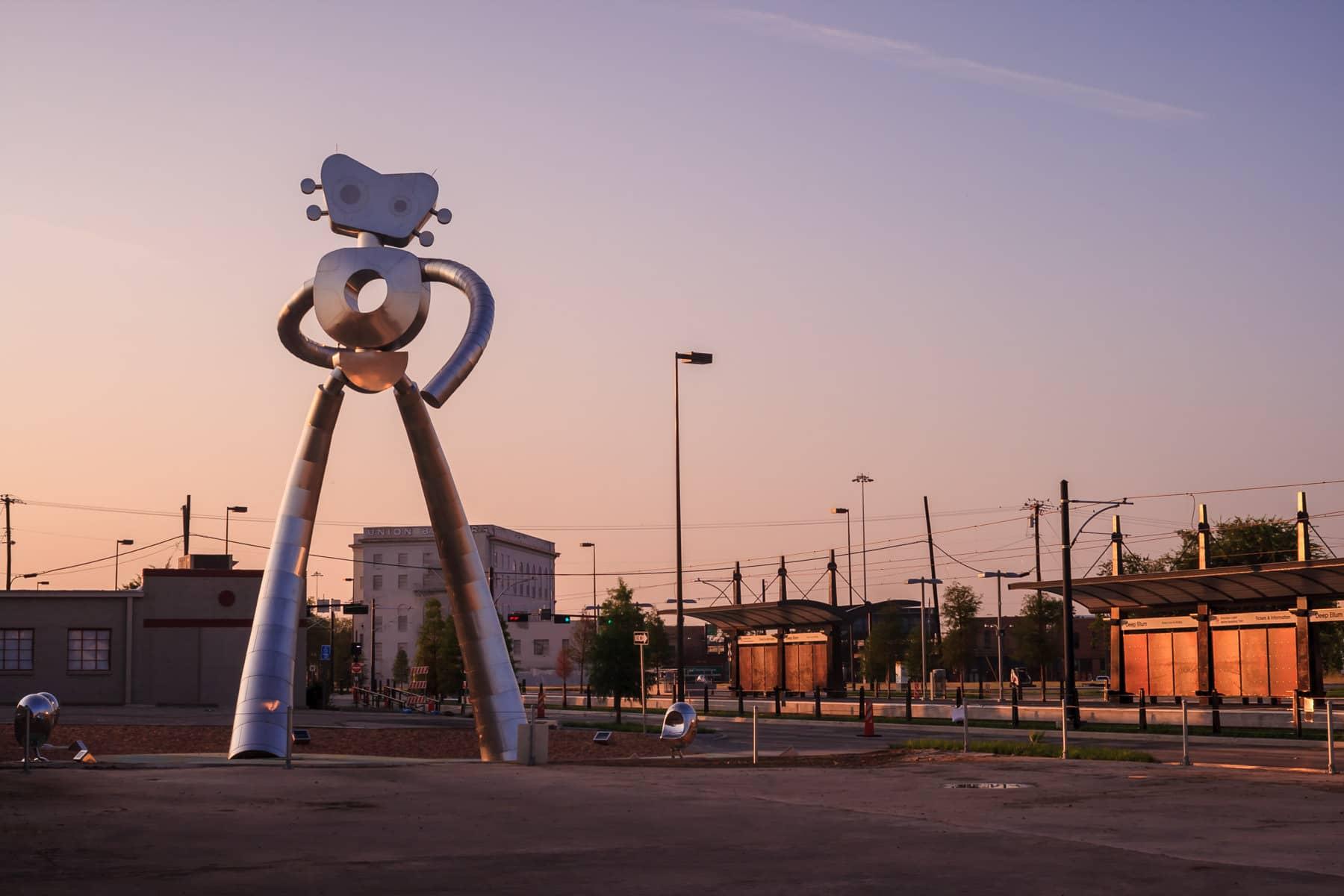 The dawn's sun lights Dallas' Traveling Man sculpture in Deep Ellum.