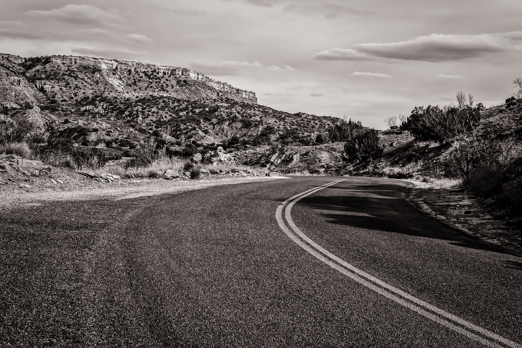 A two-lane park road winds through Palo Duro Canyon, Texas.