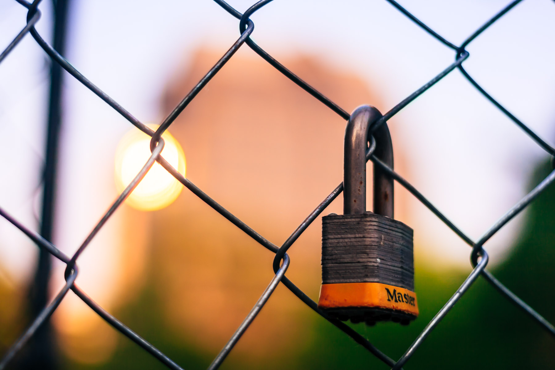 A forgotten padlock hangs from a fence in Uptown Dallas as the early morning sunlight glints off a distant building in the background.