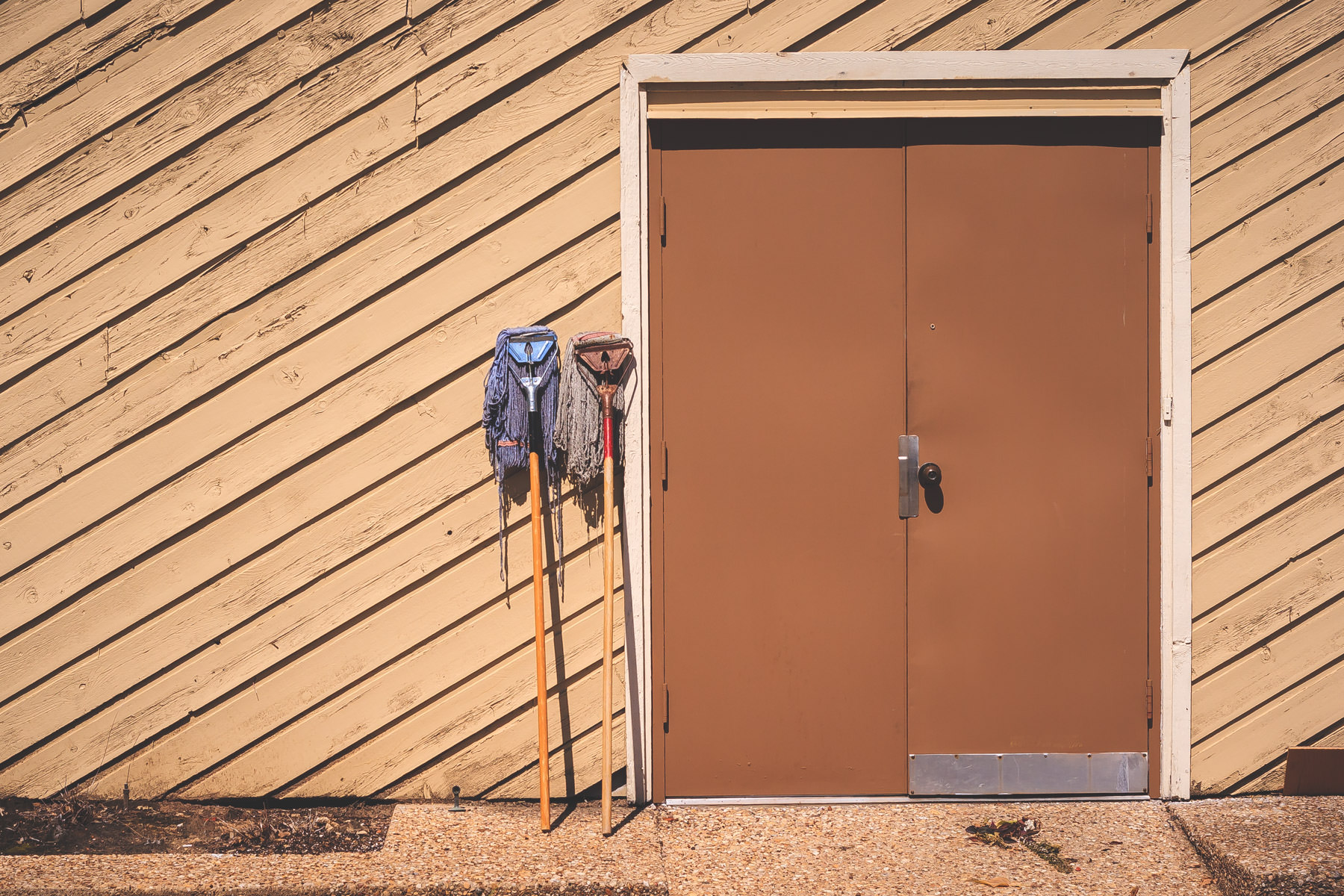 A pair of mops bake in the summer sun outside the backdoor of a business in Tyler, Texas.