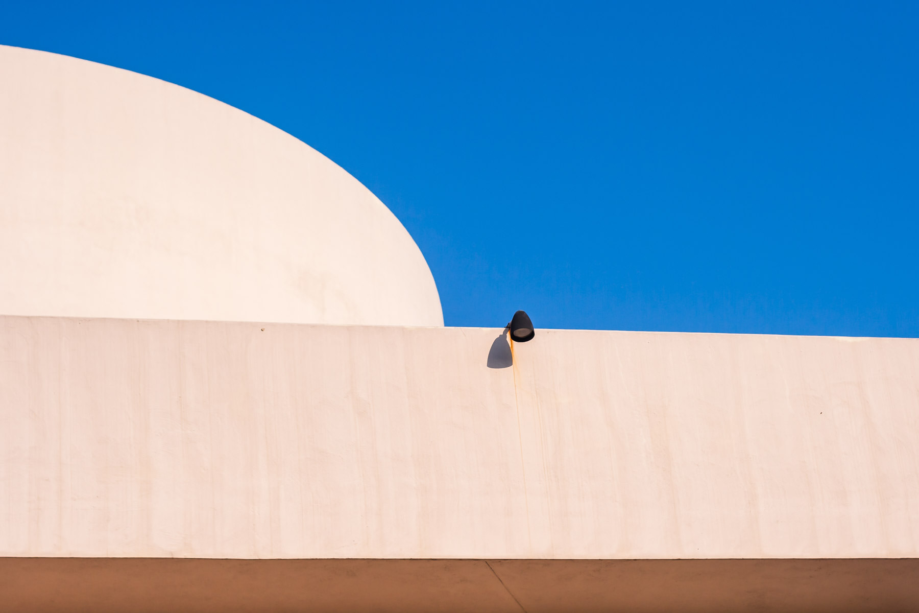 A lonesome lamp on the minimalist exterior of Dallas' Kalita Humphreys Theatre.
