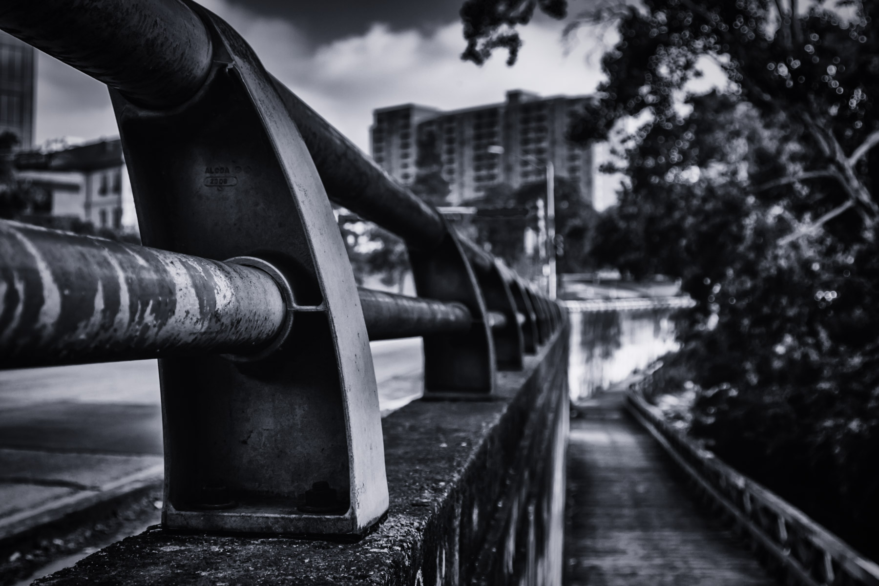 A railing along a road running along Turtle Creek in Uptown Dallas.