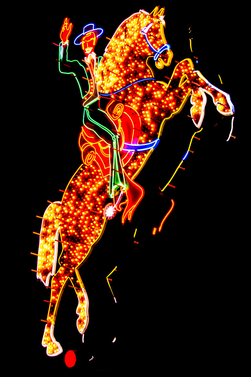 A neon sign of a cowboy riding his horse in Downtown Las Vegas.
