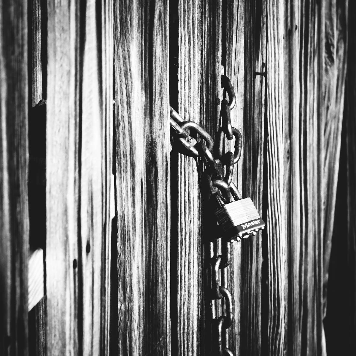 A lonely padlock hangs from a chained gate in Nacogdoches, Texas.