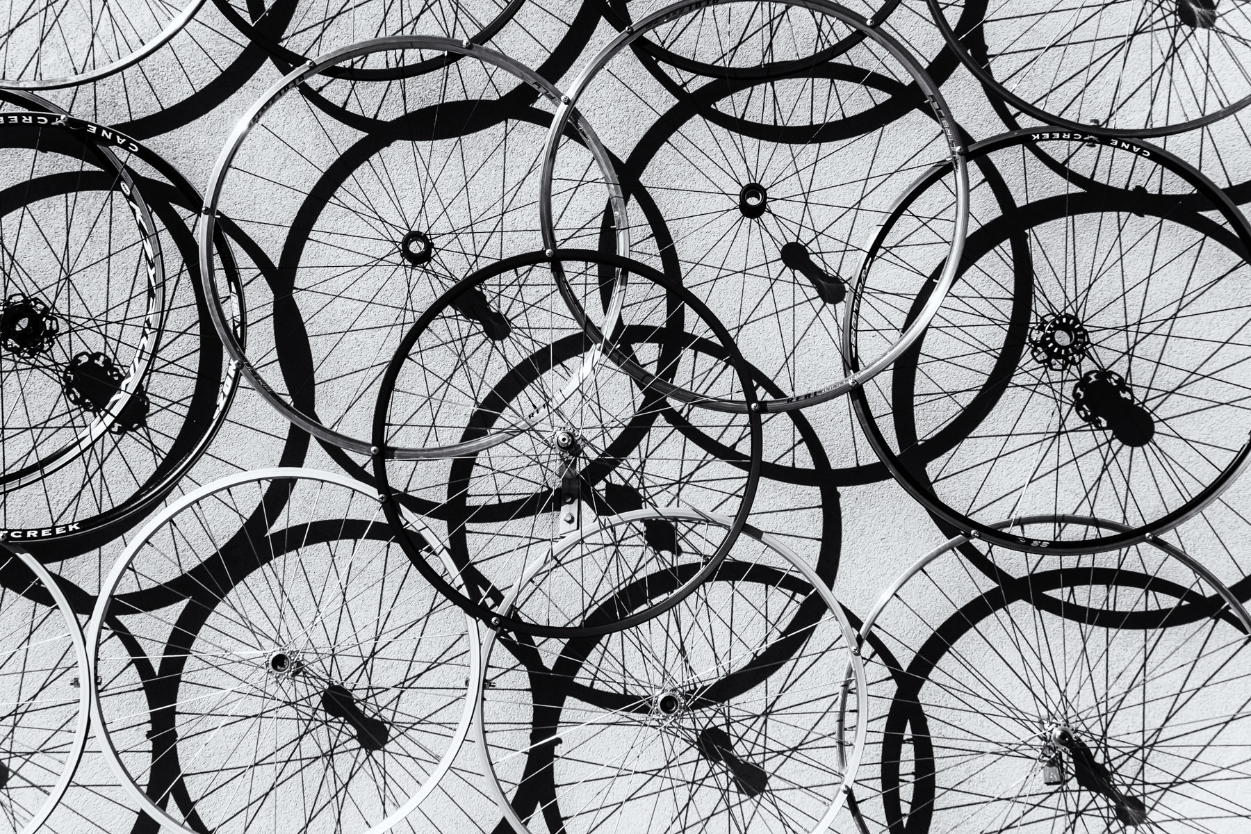 Bicycle wheels on the outside wall of a bike shop in Grapevine, Texas, make up an abstract art piece.