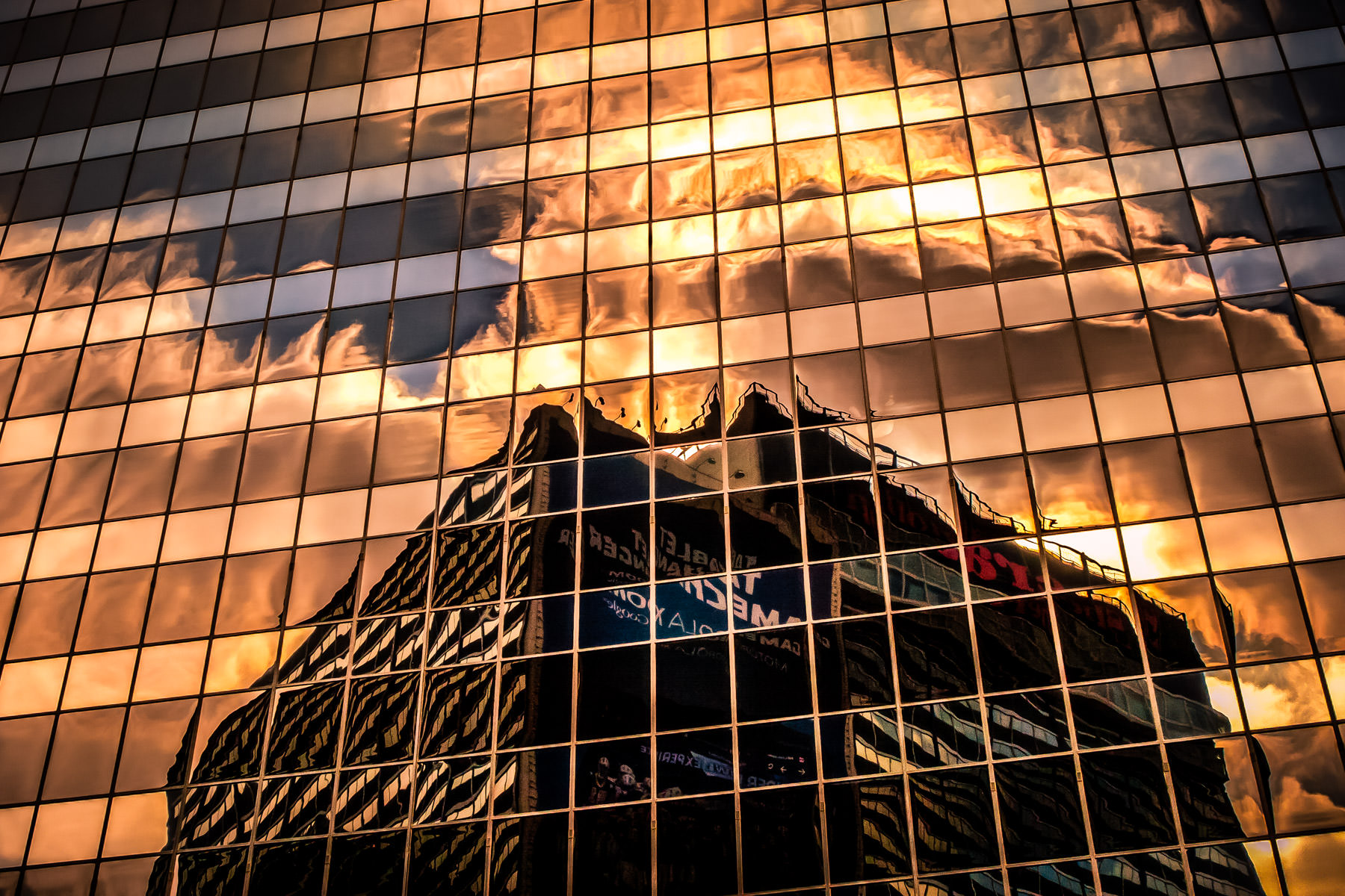 The Sheraton Hotel in Downtown Dallas is reflected—along with the afternoon sun—in an adjacent building.