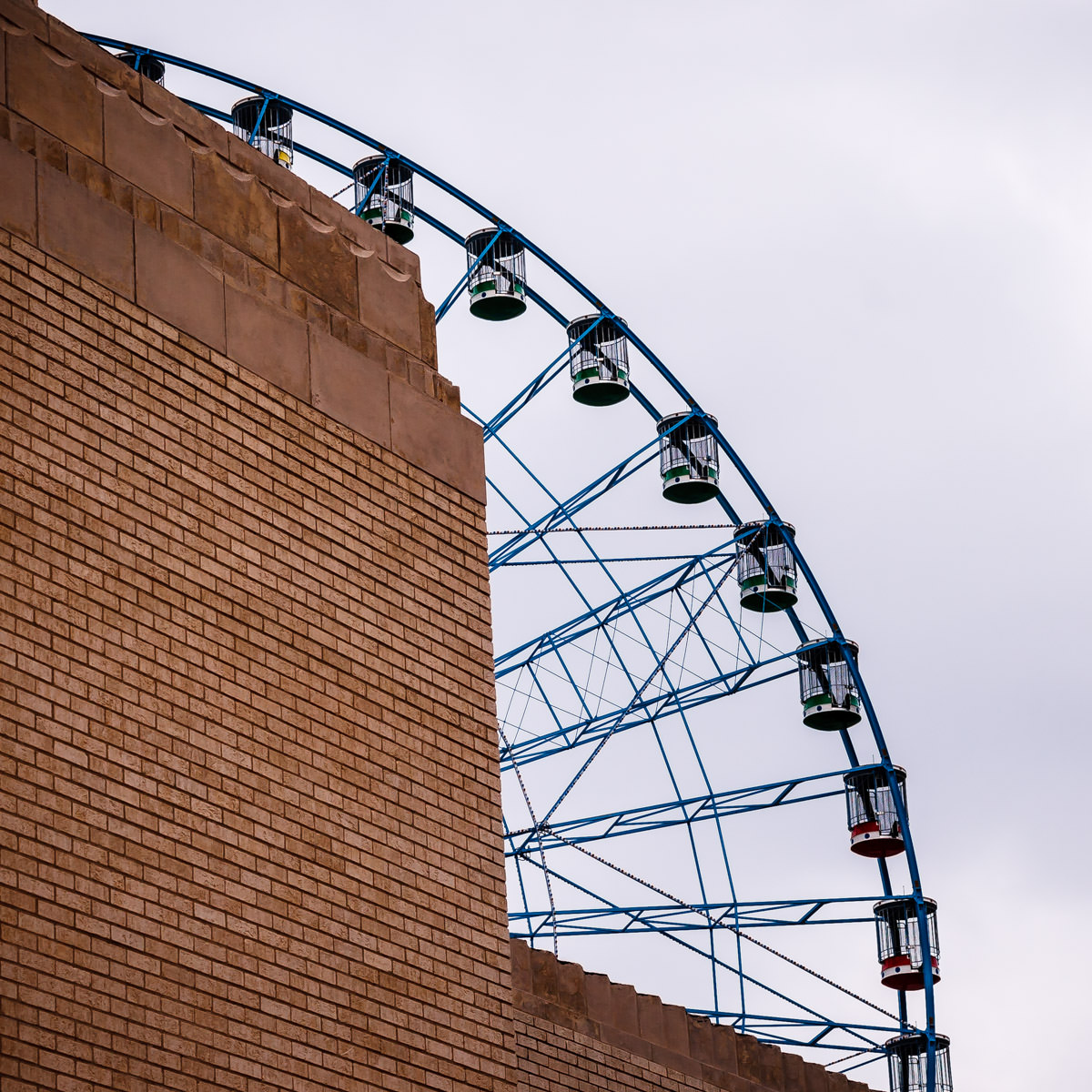 The Texas Star Ferris wheel peeks out from behind a wall of an adjacent building at Fair Park, Dallas.