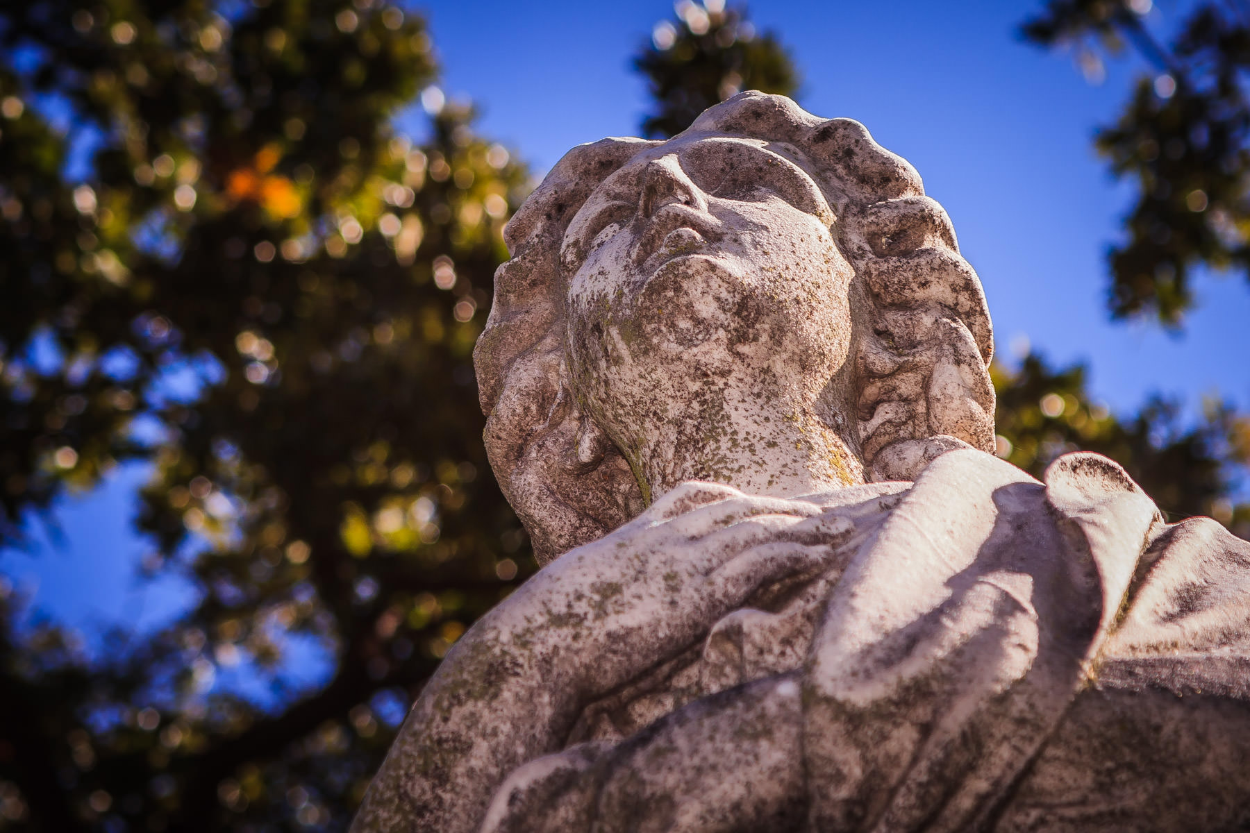 A statue looks up towards the sky at Dallas' Pioneer Park Cemetery.