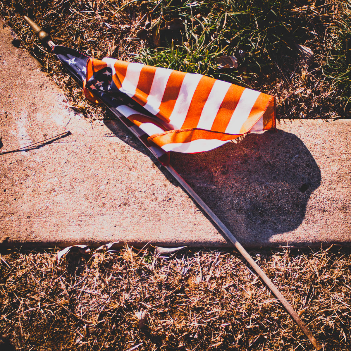 An American flag lying on the ground, fallen from a grave at Minters Chapel Cemetery, DFW Airport, Texas.