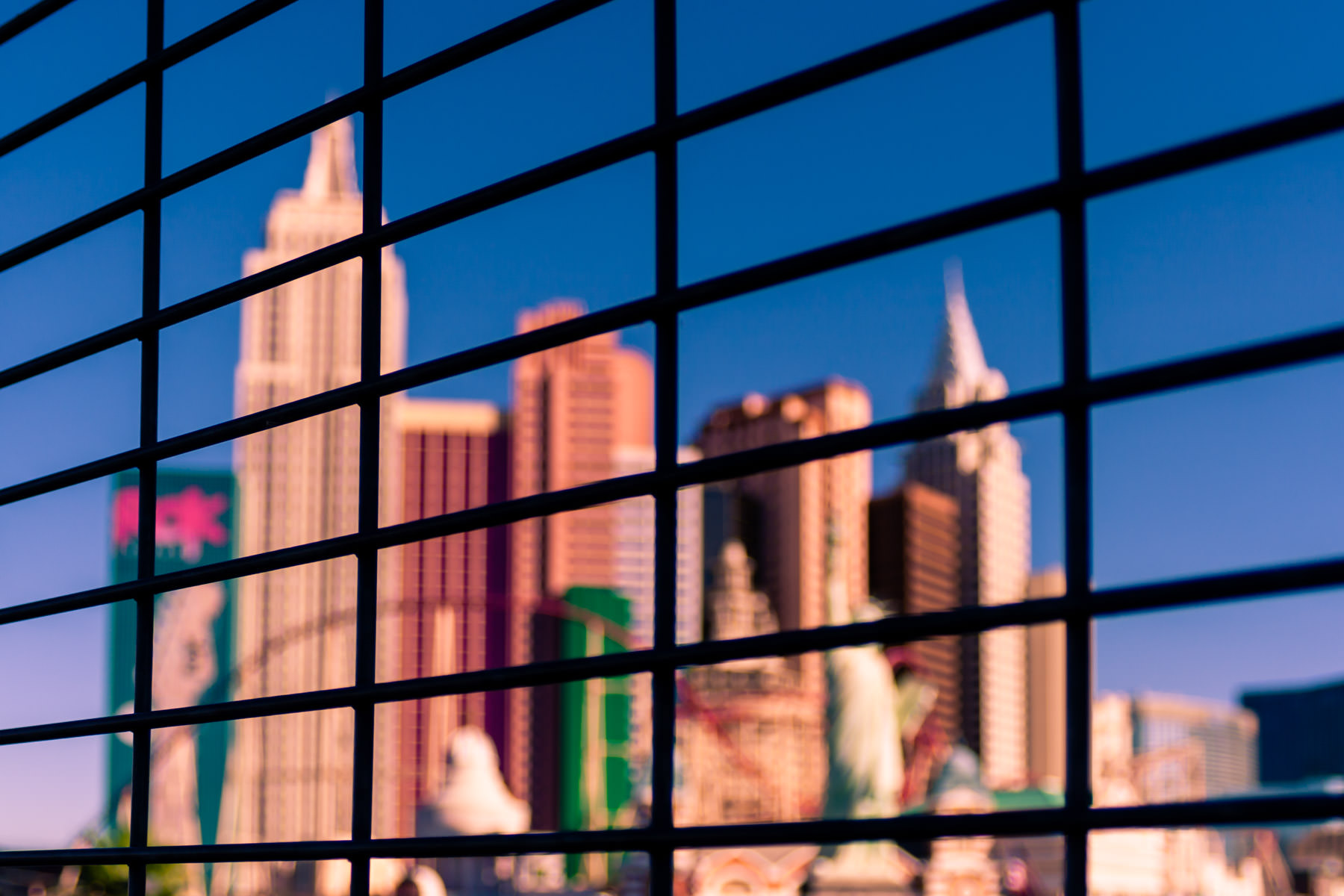 Las Vegas' New York New York Hotel and Casino as seen through the grid of a pedestrian bridge's fencing over Las Vegas Boulevard.