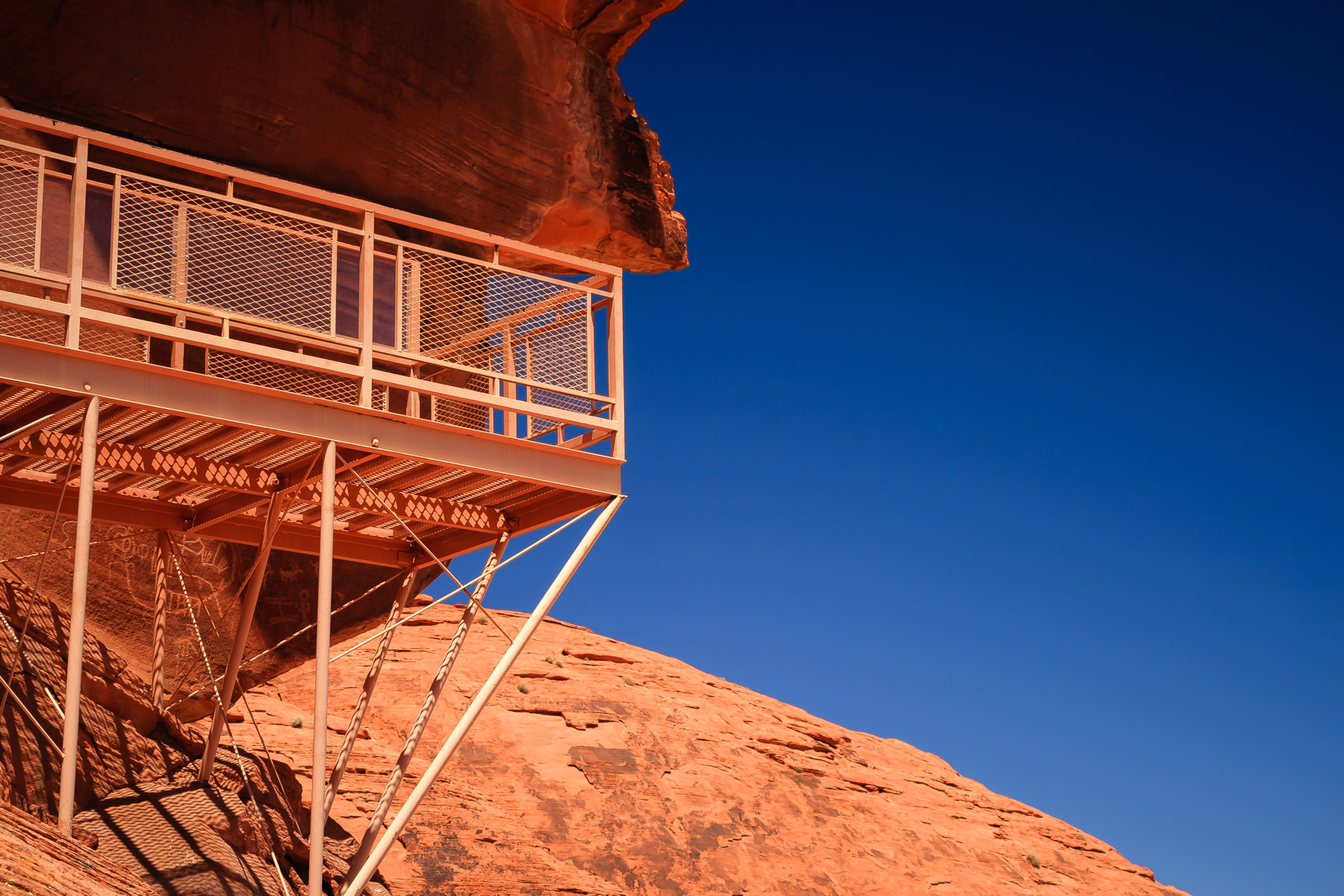 A viewing platform at the Valley of Fire's Atlatl Rock to facilitate closer looks at ancient petroglyphs (rock drawings).  In this shot, you can see a few directly underneath the platform behind its legs.