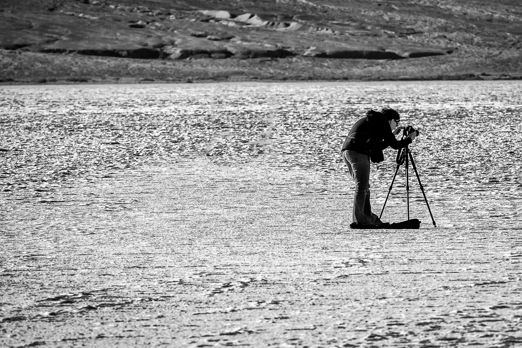 A fellow photographer prepares to take a photograph on the immense salt flats of Death Valley's Badwater Basin—the lowest point of North America at −282 feet (−86.0 m) below sea level.