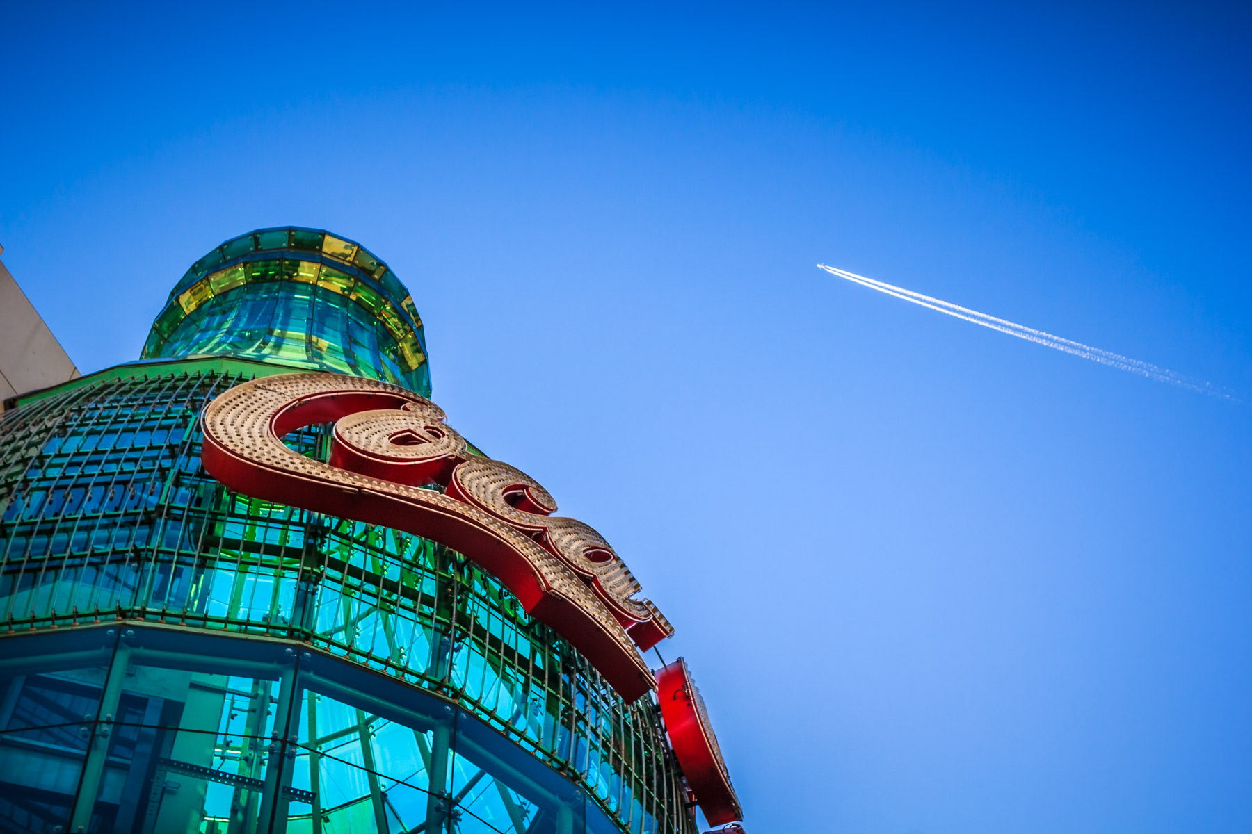 A jet flies high over the Las Vegas Valley and the Everything Coca-Cola Store on The Strip.