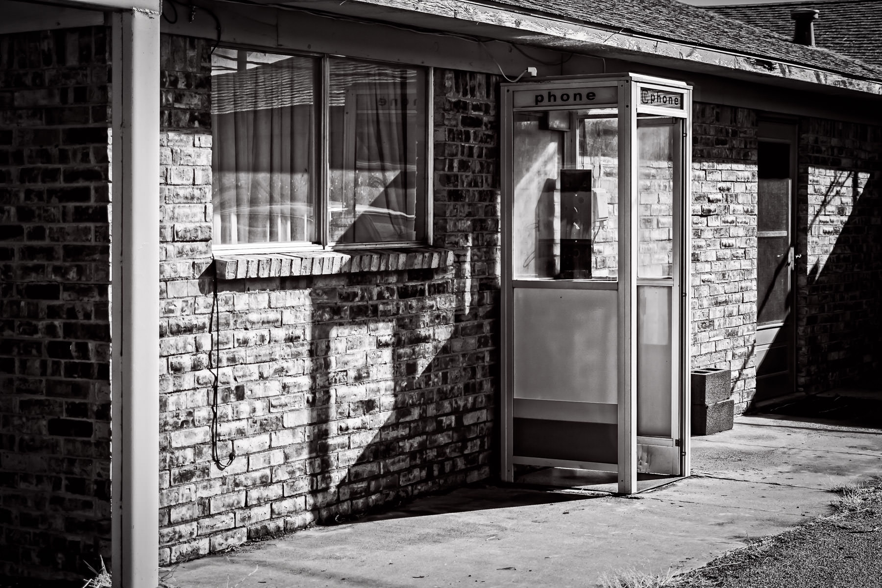 An obsolete phone booth spotted at a motel in the tiny Texas Panhandle town of Adrian.