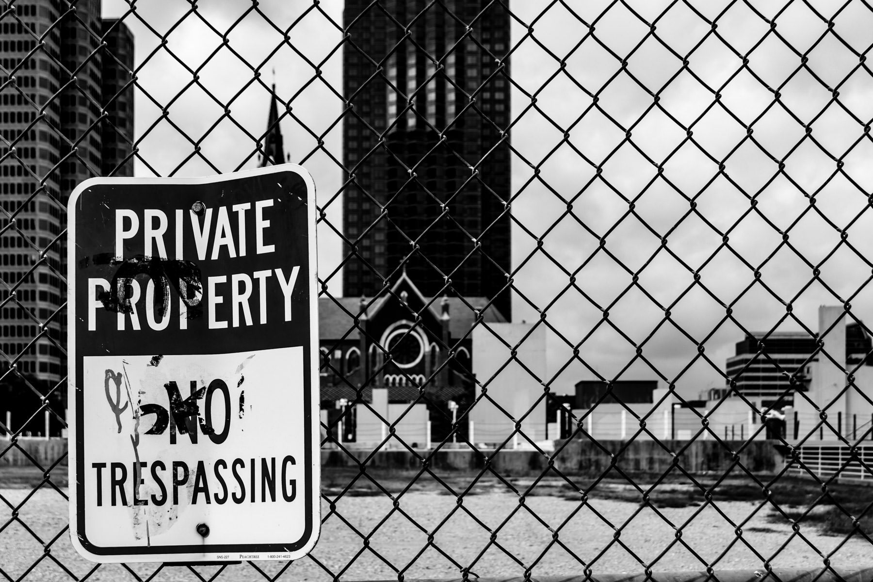 A private property sign on a fence spotted in the Dallas Arts District.