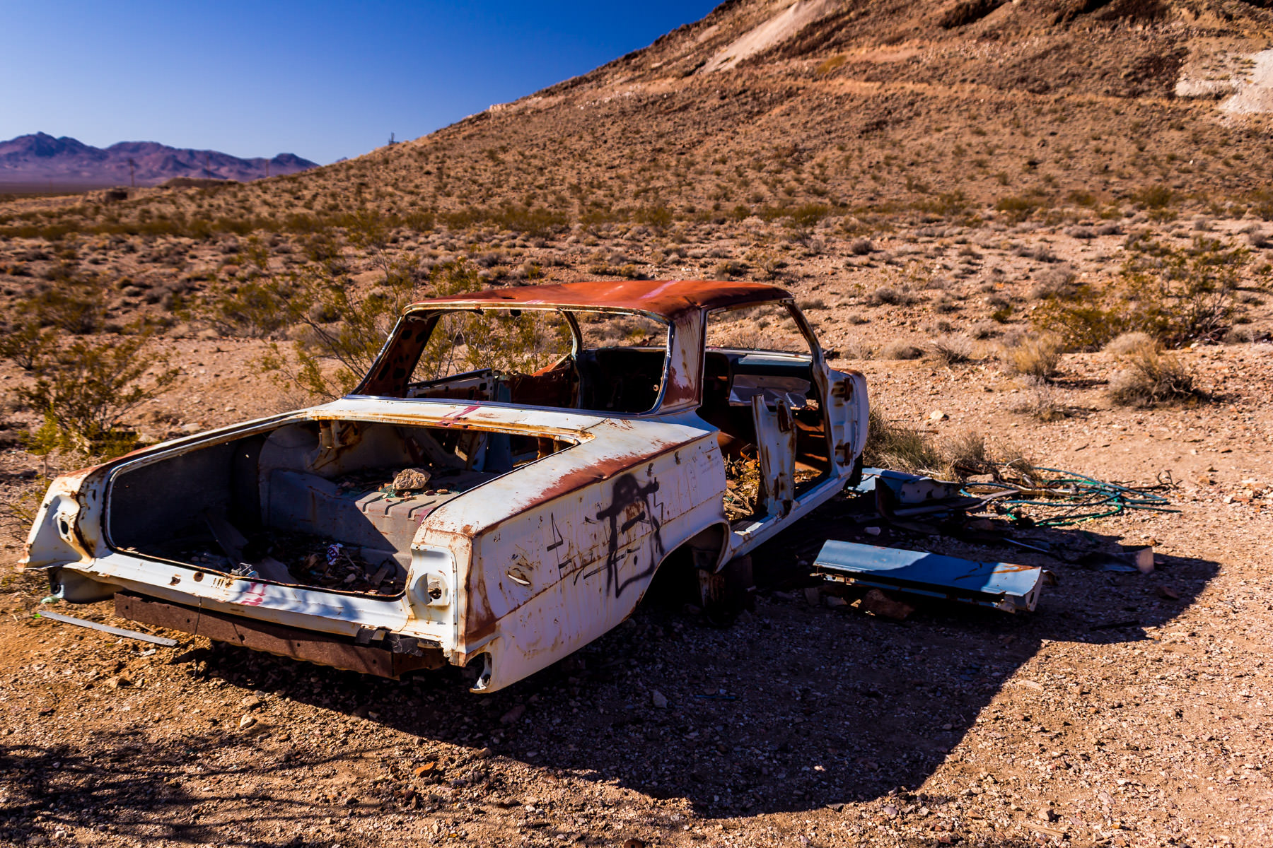 An abandoned Chevy Impala left to the elements in the middle of the vast, desolate Nevada desert near the border with California.