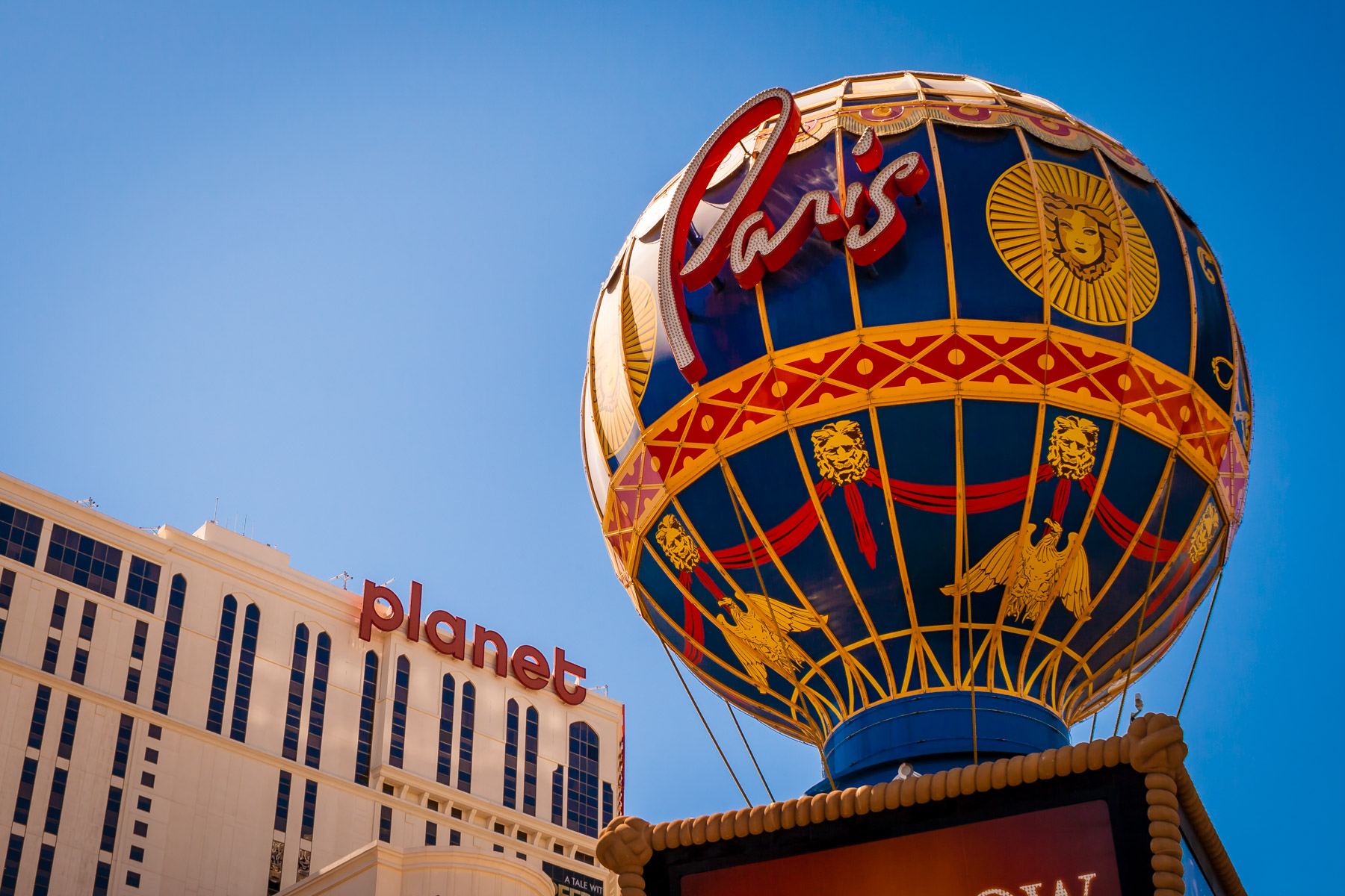 The balloon-shaped sign at Paris Hotel & Casino with Planet Hollywood in the background, Las Vegas.