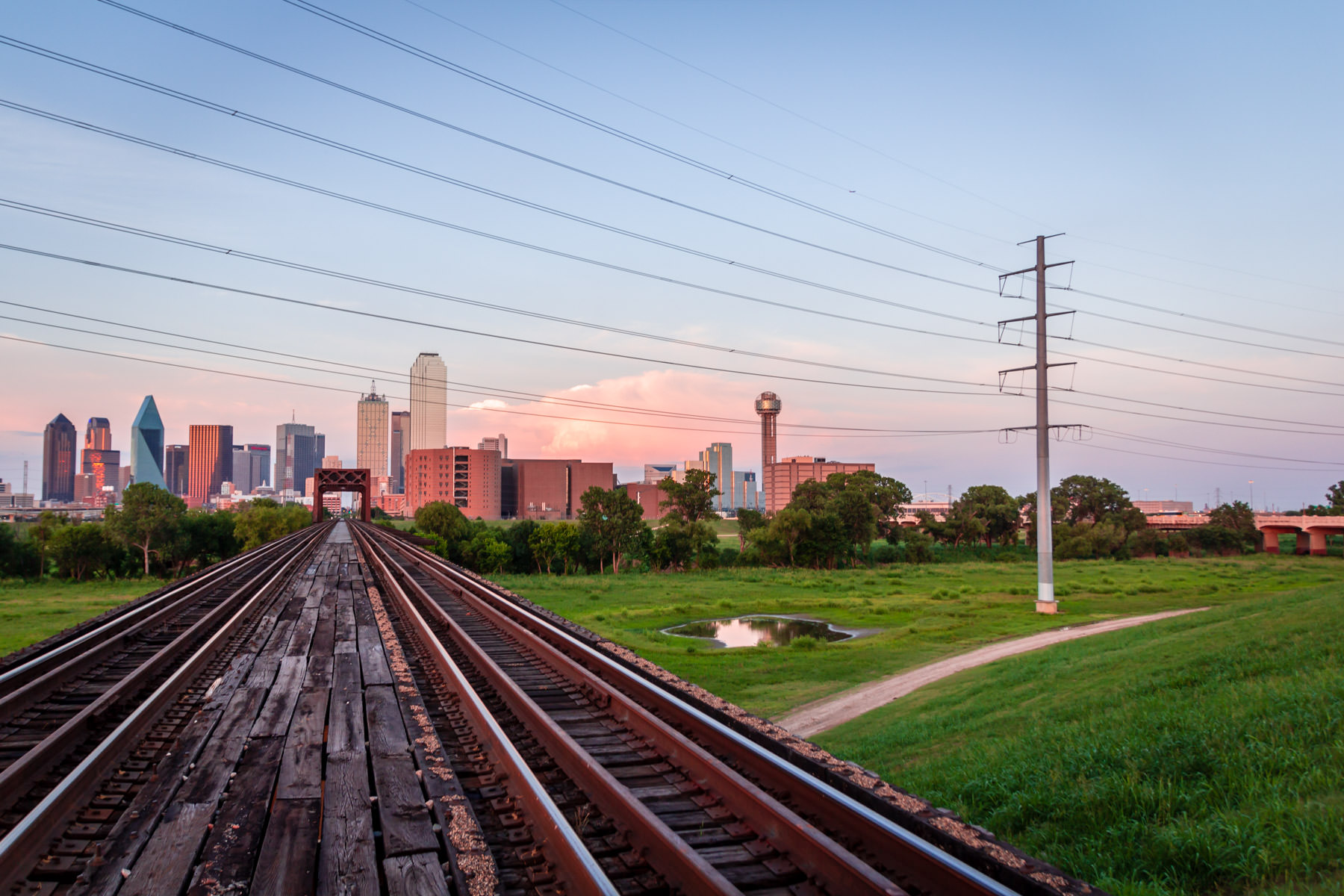 Train tracks lead to Downtown Dallas over the Trinity River floodplain as the sun sets on North Texas.