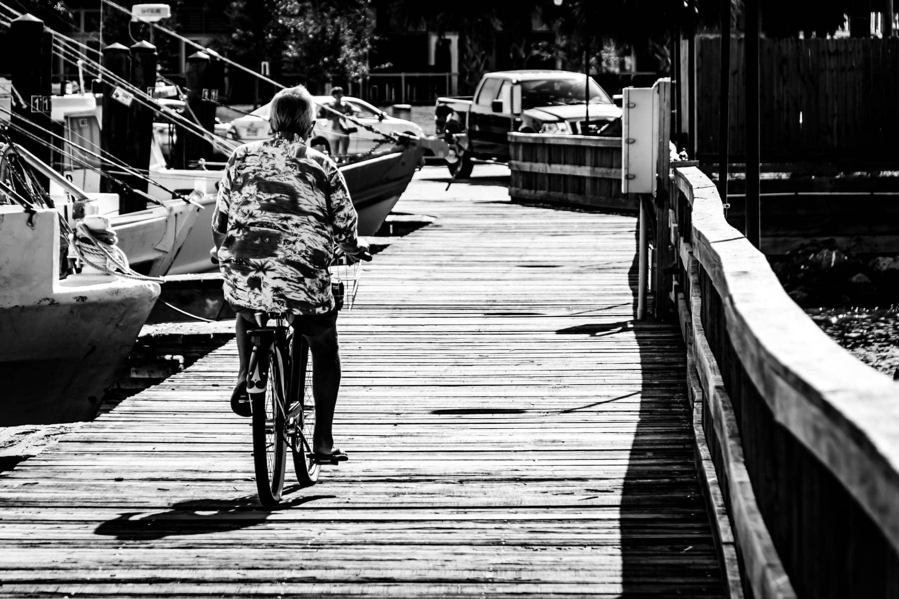 A Hawaiian-shirted gentleman rides a bike along a pier in Galveston, Texas.