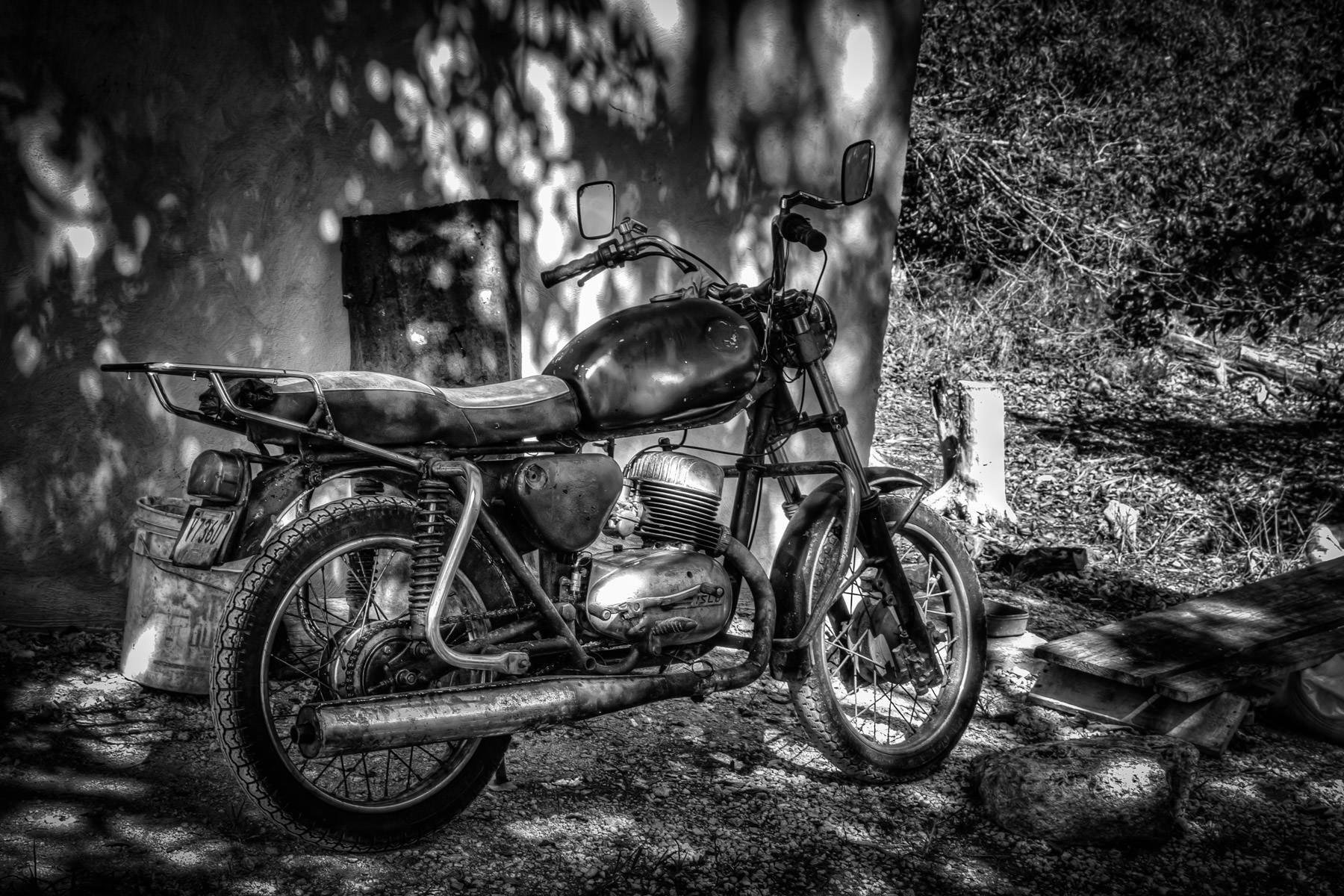 A rusted motorcycle parked outside a shed at the Mayan archaeological site of Xcambo, Yucatán, Mexico.