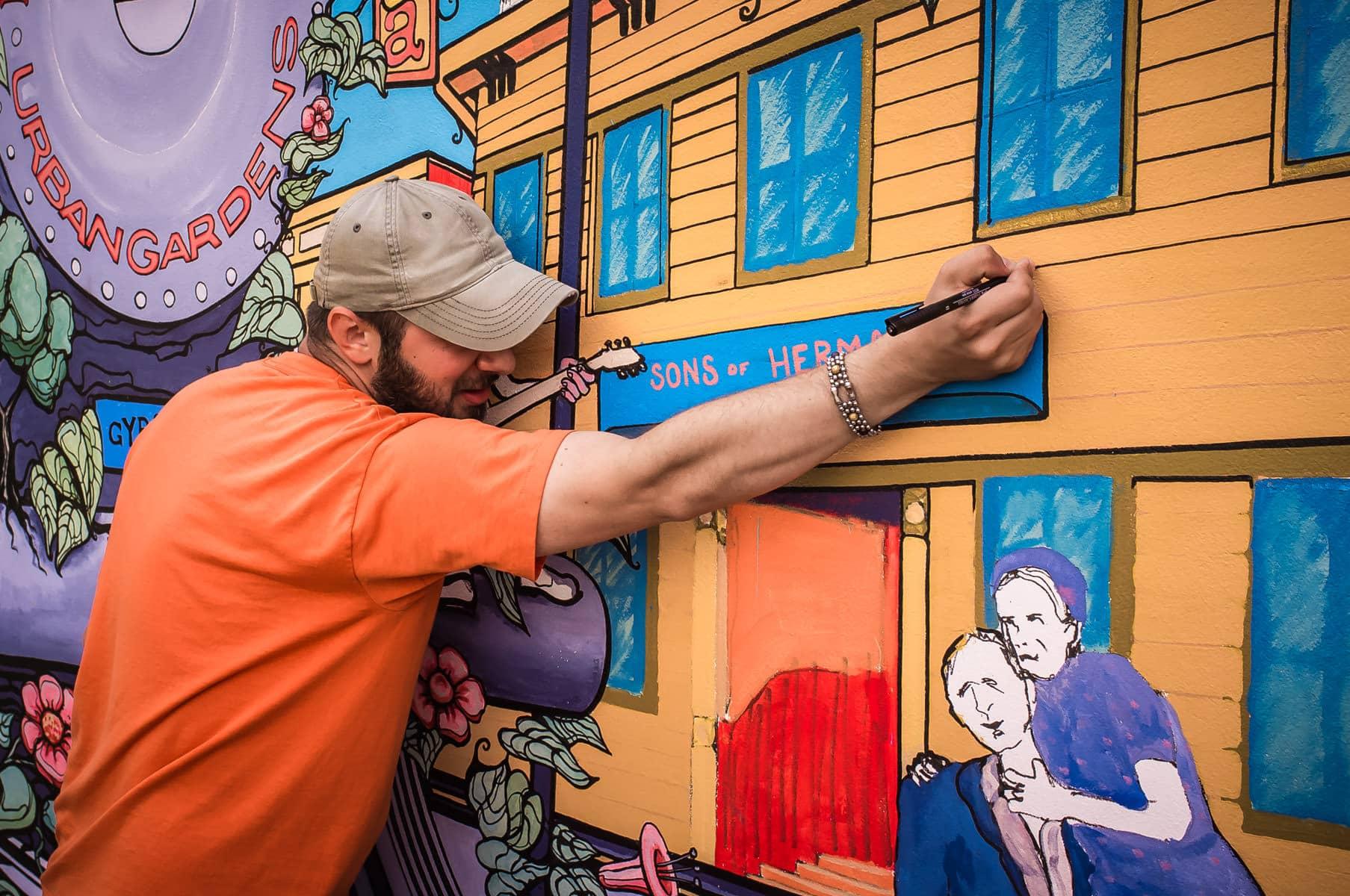 Artist Dan Colcer works on a mural at Dallas' Deep Ellum Urban Gardens.