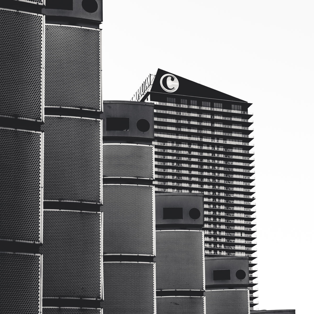 The Cosmopolitan of Las Vegas is partially obscured by decorative structures in front of Bally's.