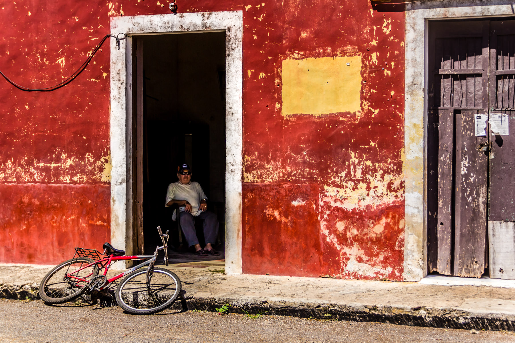 An older gentleman seeks relief from the relentless sun in the tiny Yucatan town of Dzemul, Mexico.