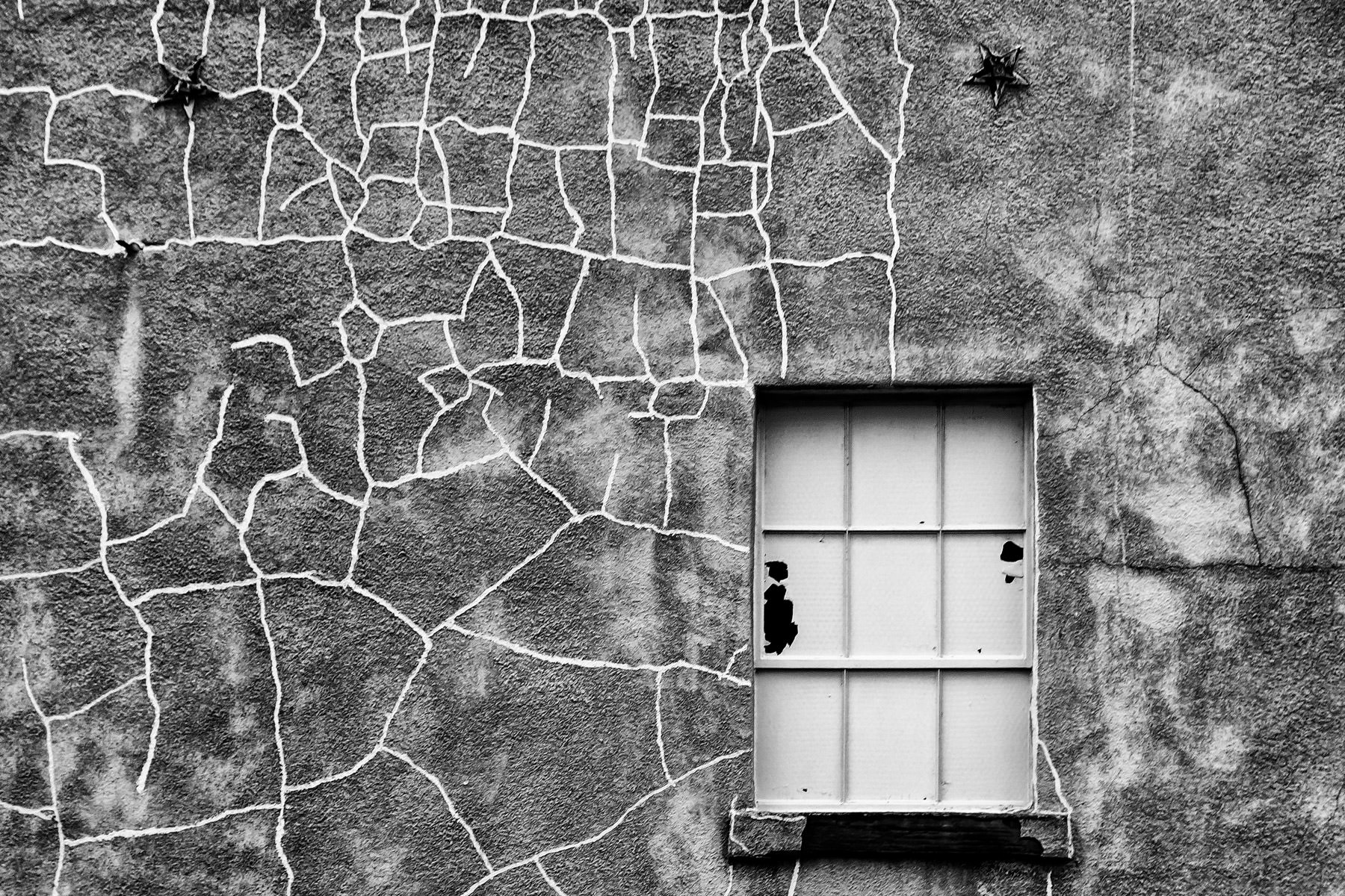 A cracked wall that's been patched numerous times, spotted in Downtown McKinney, Texas.