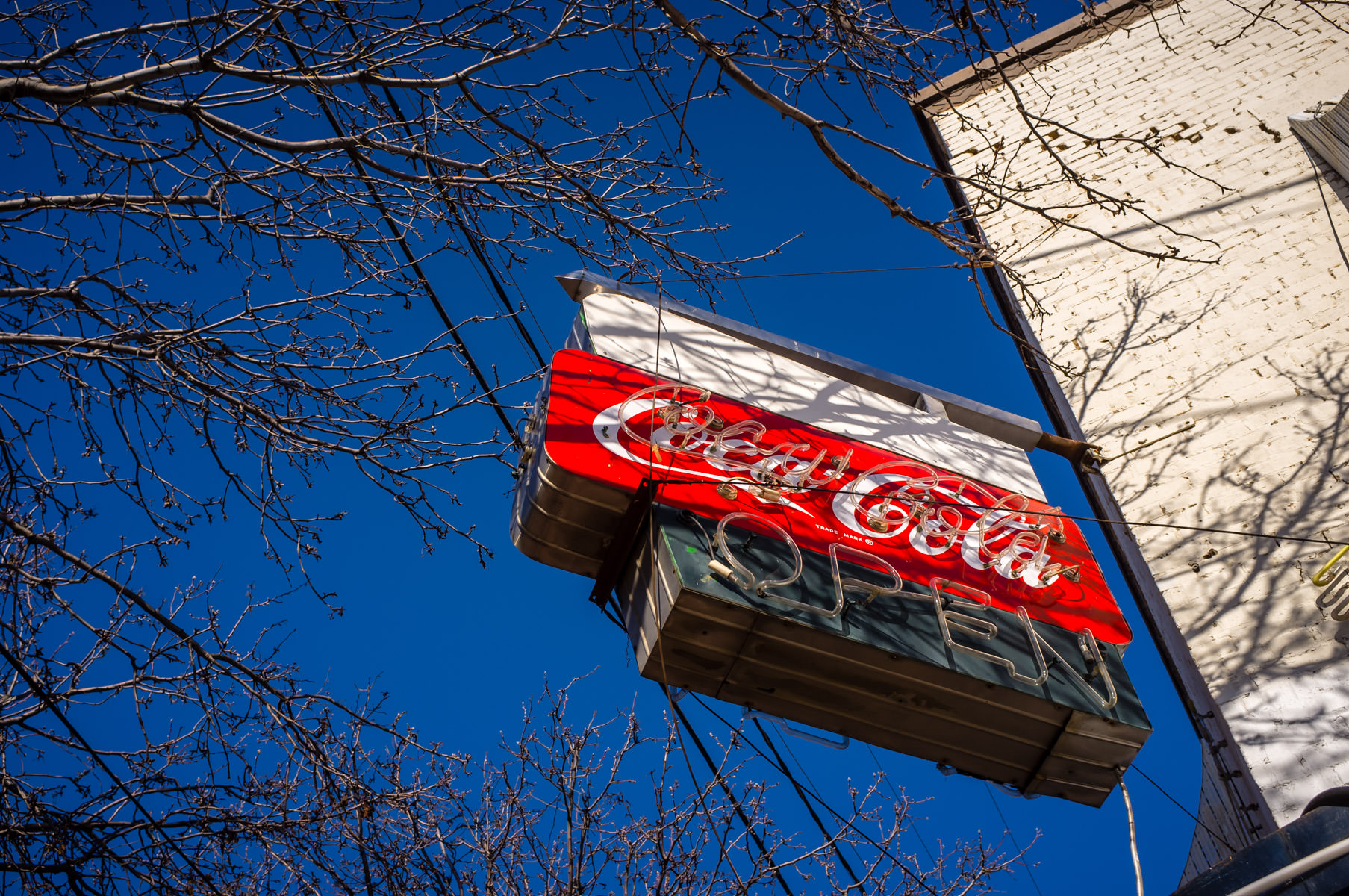 An old Coca-Cola sign on the side of a restaurant at the Dallas Farmers Market.