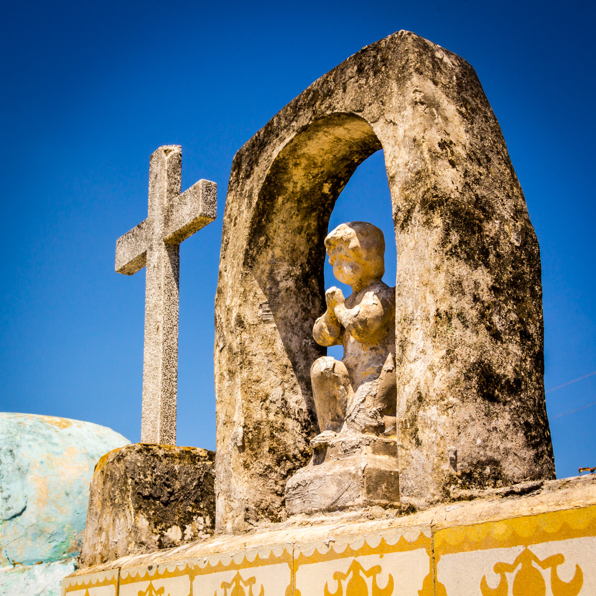 A cherubic statue atop a grave in a cemetery in the Yucatan town of Dzemul, Mexico.