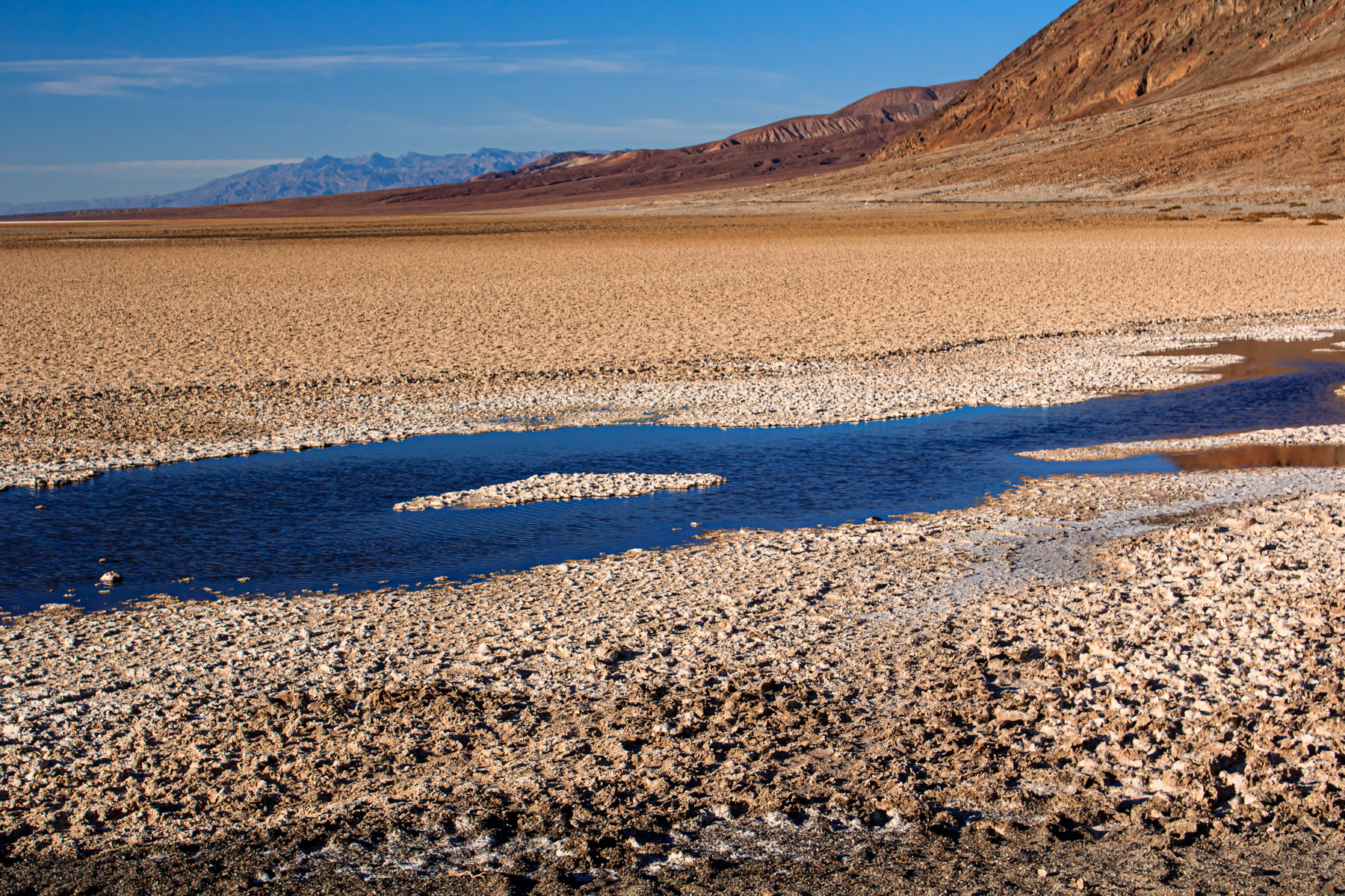 A rapidly-evaporating pond left by a recent rainfall at Badwater Basin—the lowest point in North America—at Death Valley National Park, California.