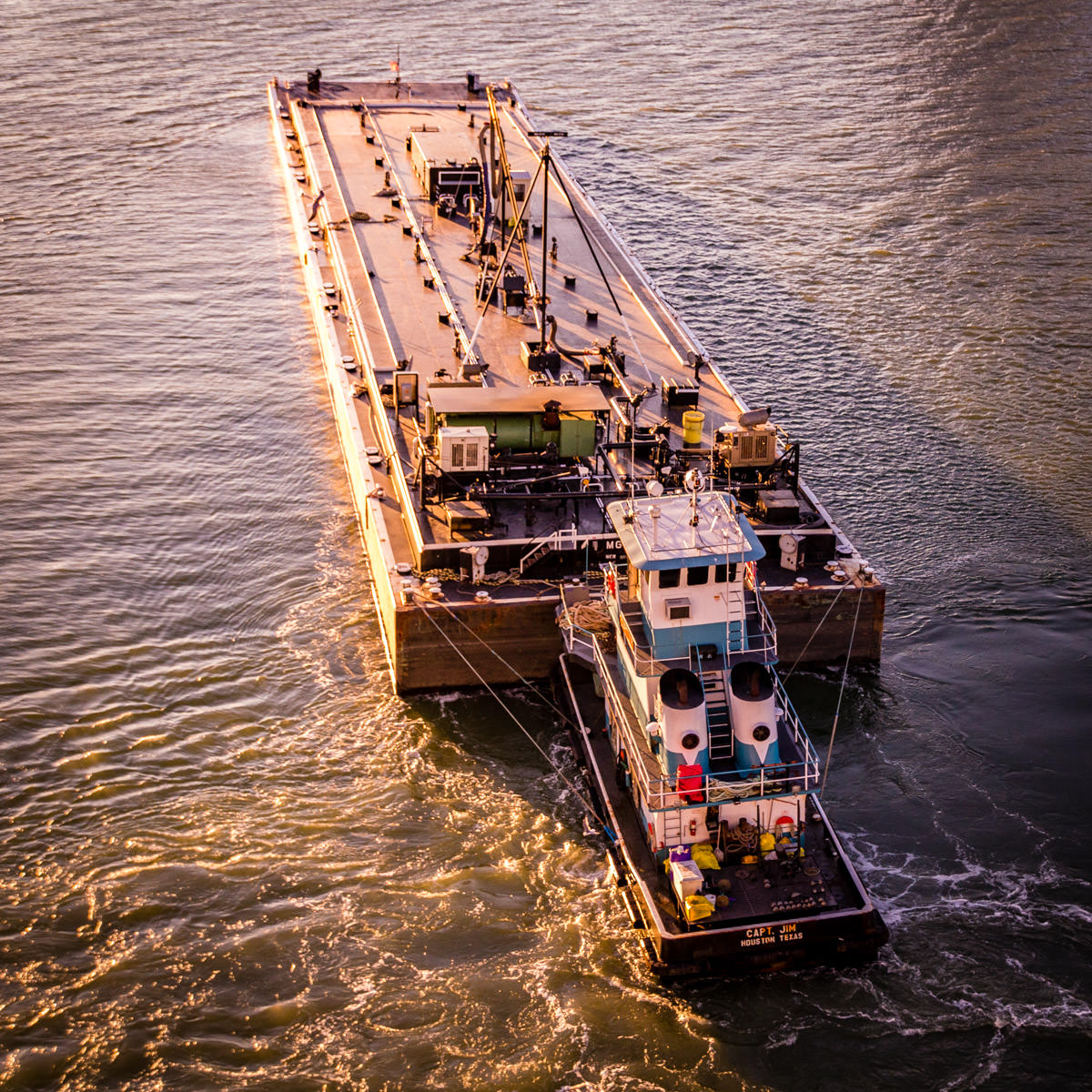 A fuel barge is pushed by a towboat as the sun sets over the Port of Galveston, Texas.