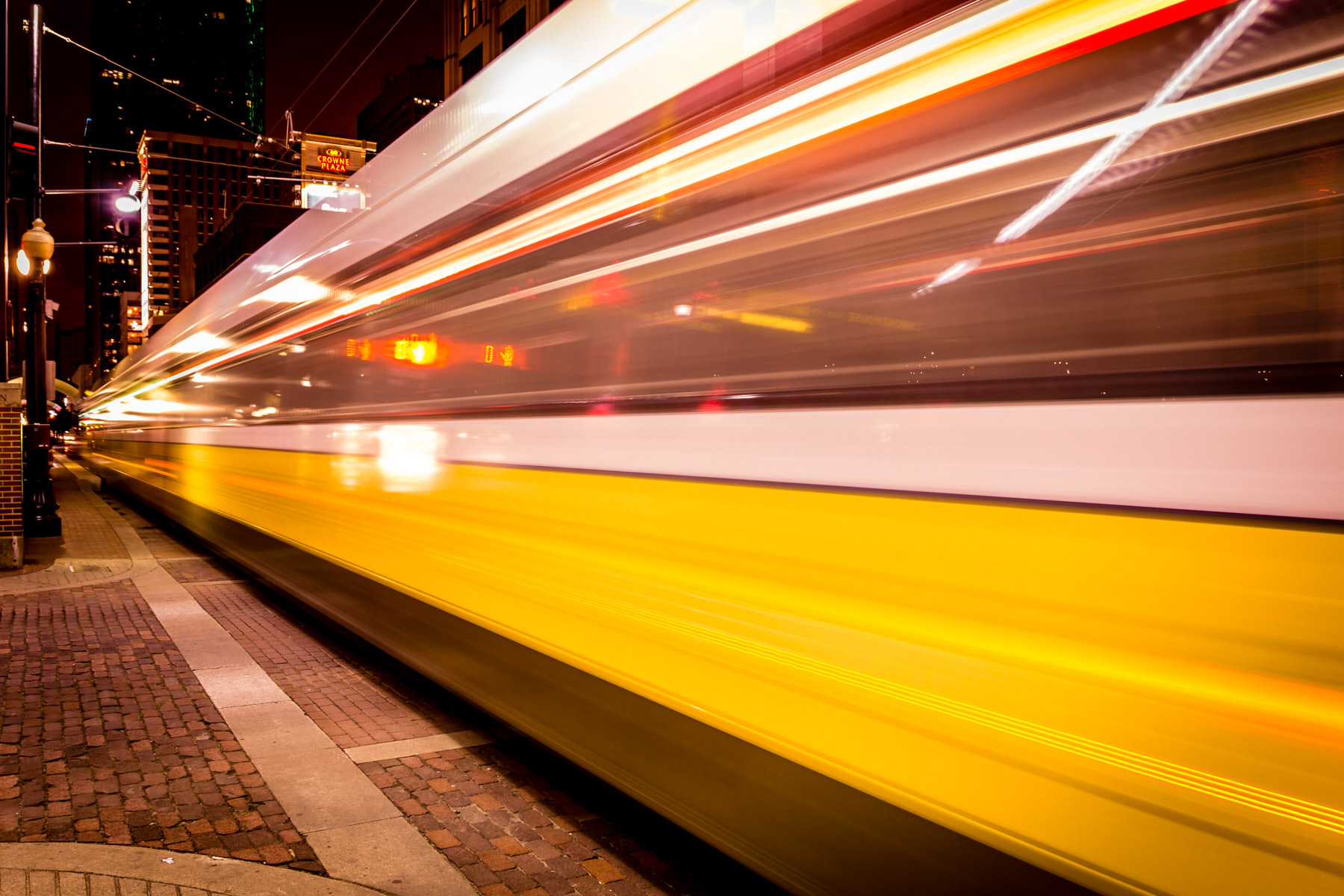 A DART train speeds through Downtown Dallas in this long exposure night shot.