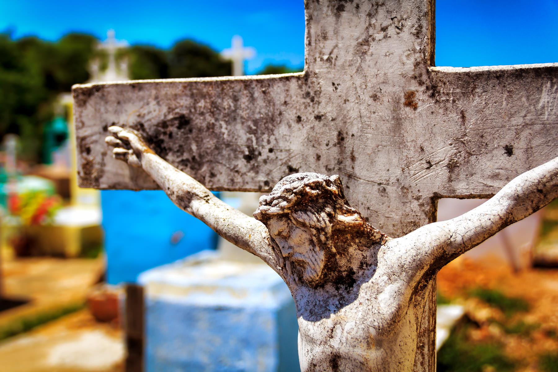 A crucifix atop a gravestone in a cemetery in the tiny Mayan town of Dzemul, Yucatan, Mexico.