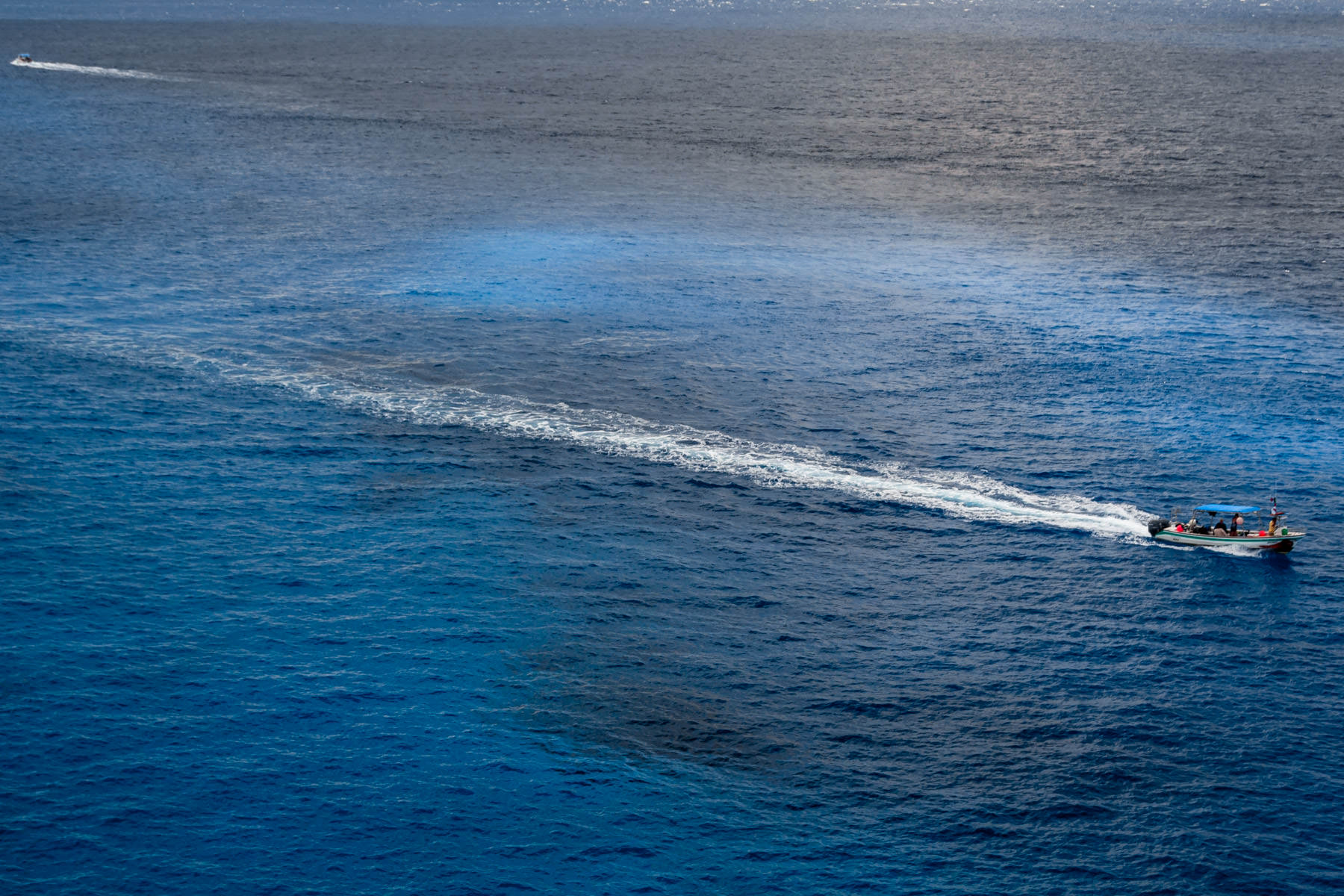 A boat cuts through blue waters just off the coast of Cozumel, Mexico.