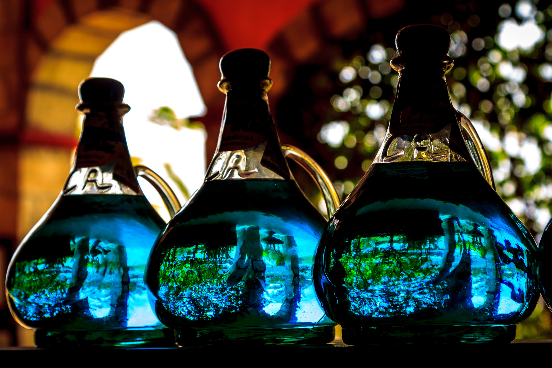 Sunlight refracts through jugs of blue tequila at the Cava Antigua tequila store in Cozumel, Mexico.
