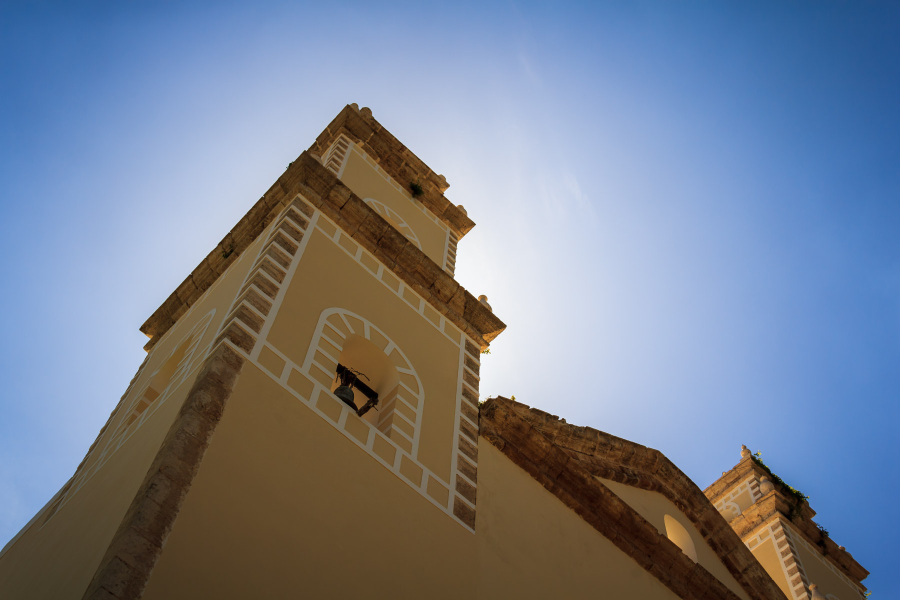 The steeple of the Catholic church in the tiny town of Dzemul, Yucatan, Mexico, obscures the midday sun.