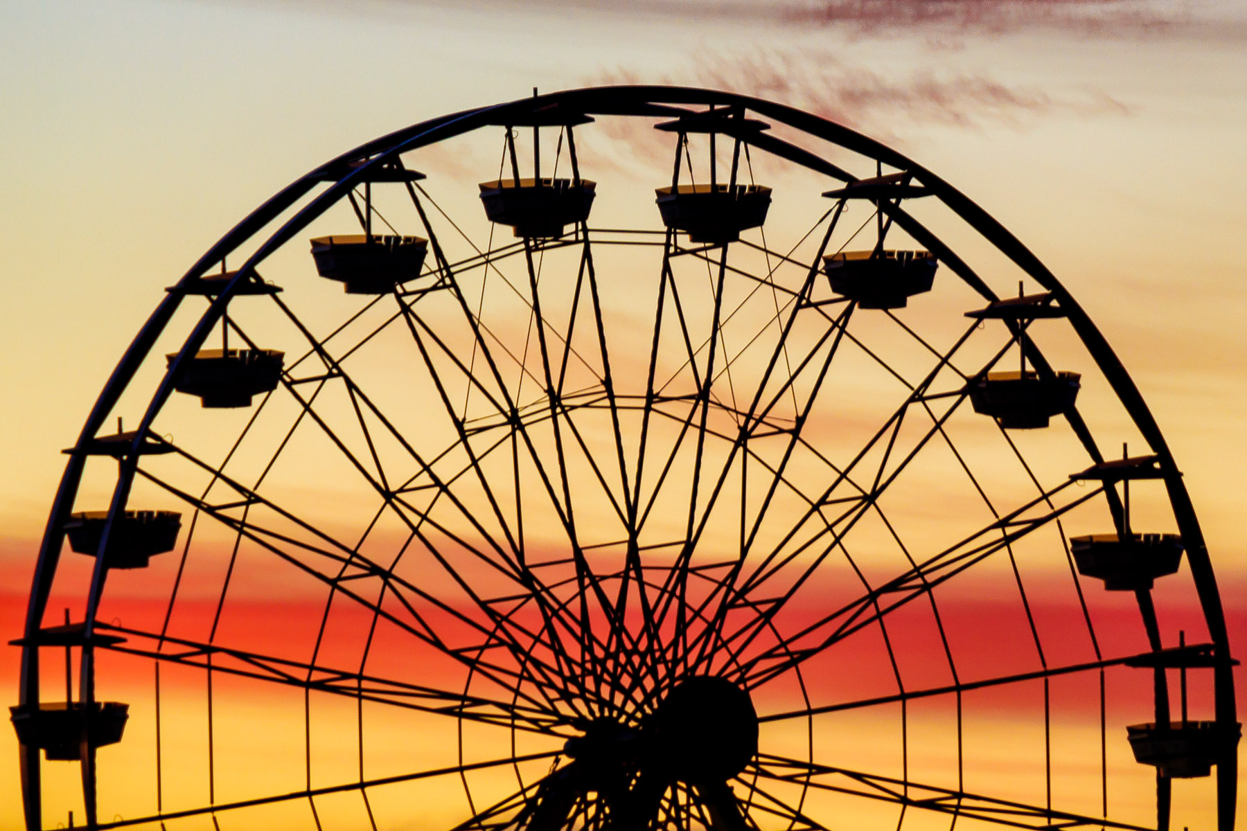 Detail of the Ferris wheel on Galveston, Texas' pleasure pier as the sun rises over the Gulf of Mexico.