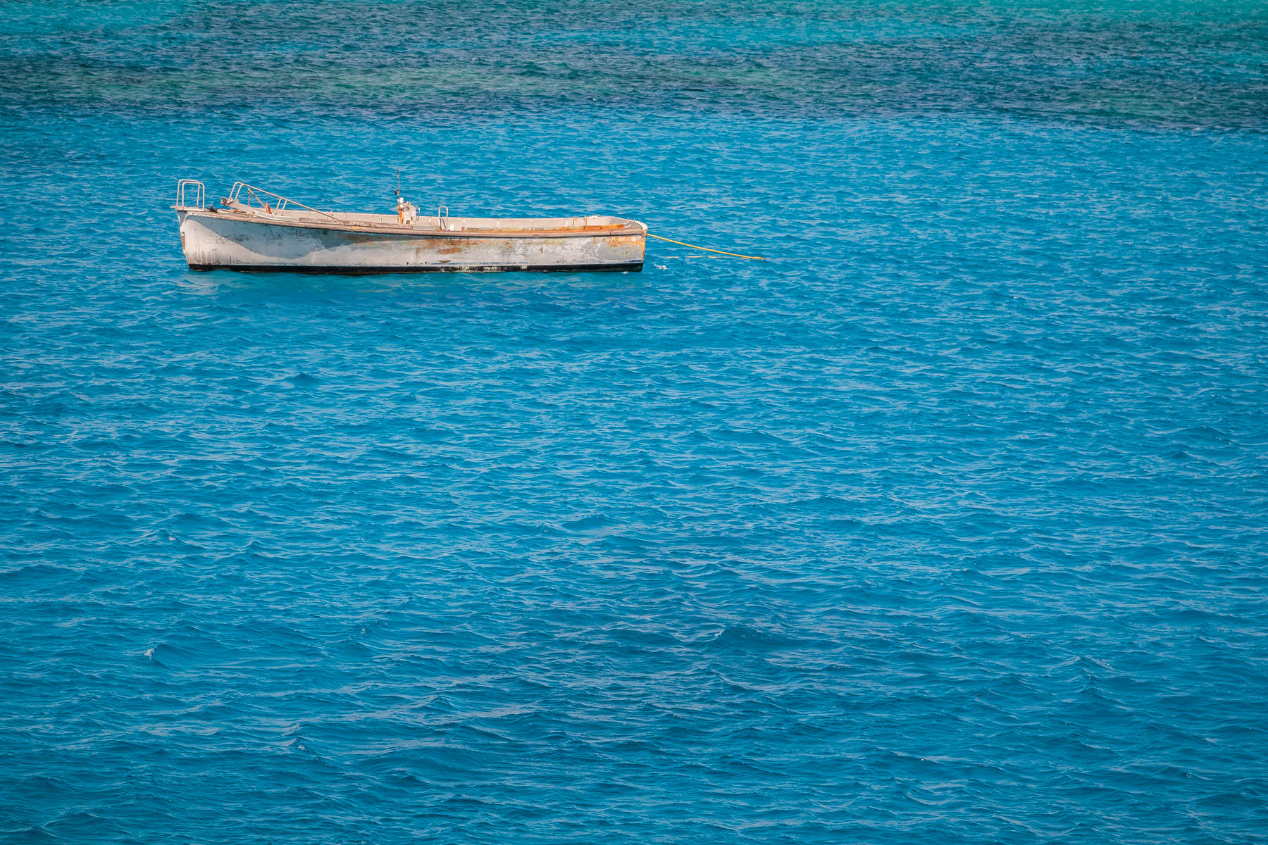 A boat floats in the Caribbean Sea just off the coast of George Town, Grand Cayman.