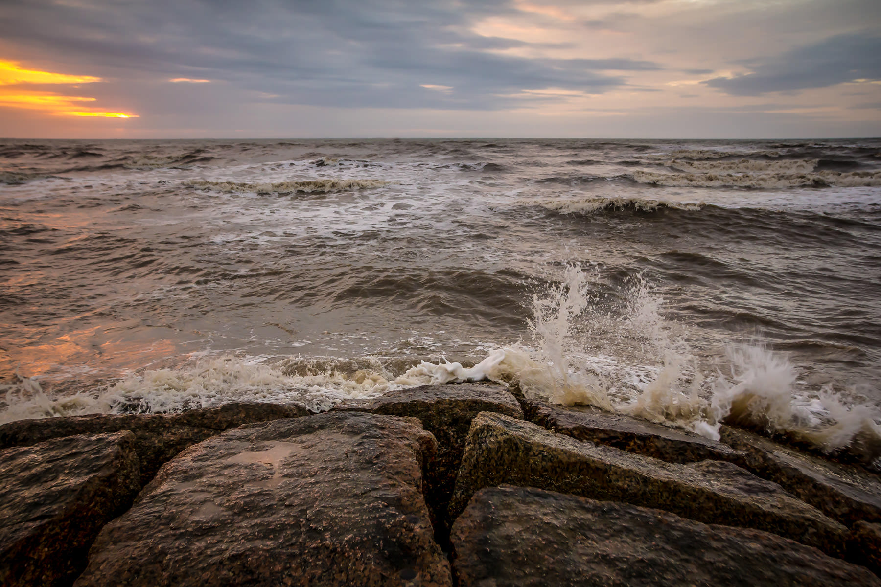 Early morning surf crashes into a granite groyne on the Galveston, Texas beach.