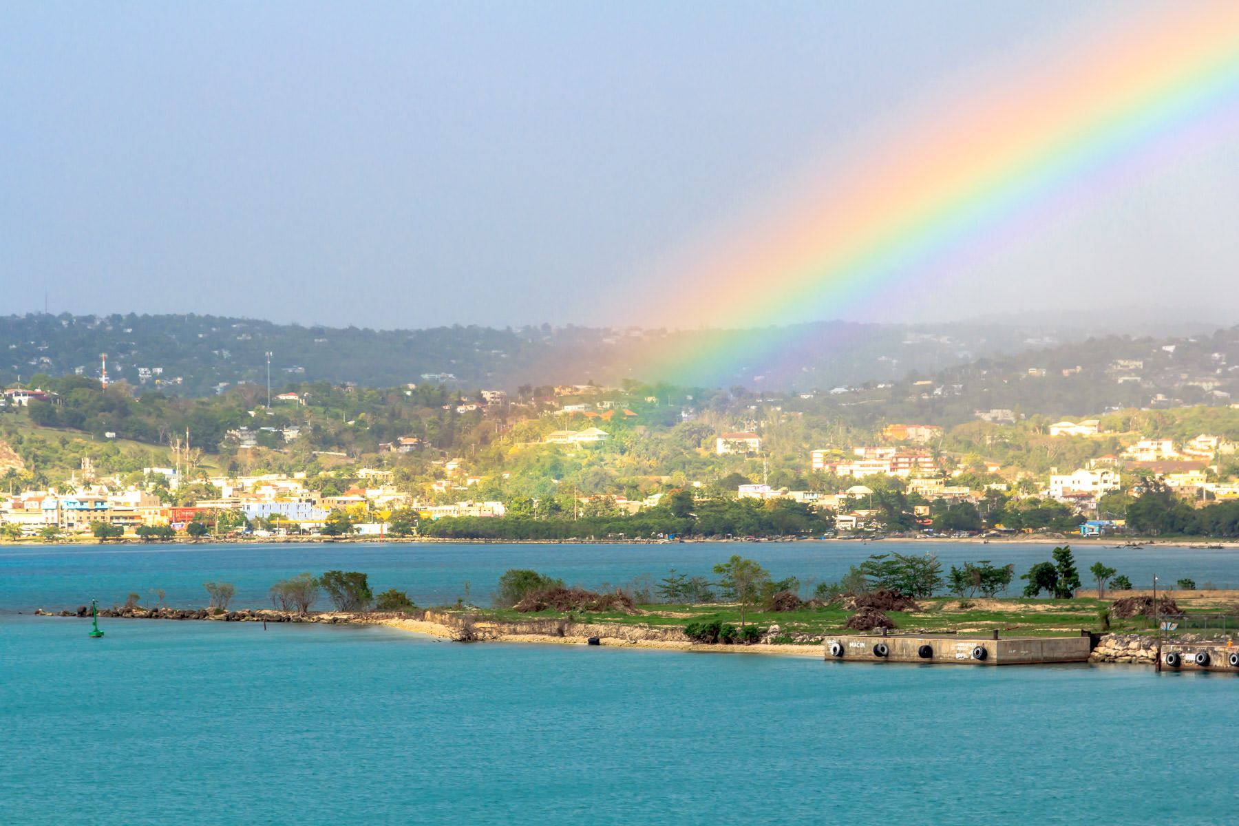 A rainbow—remnants of an afternoon shower—arcs over Montego Bay, Jamaica.