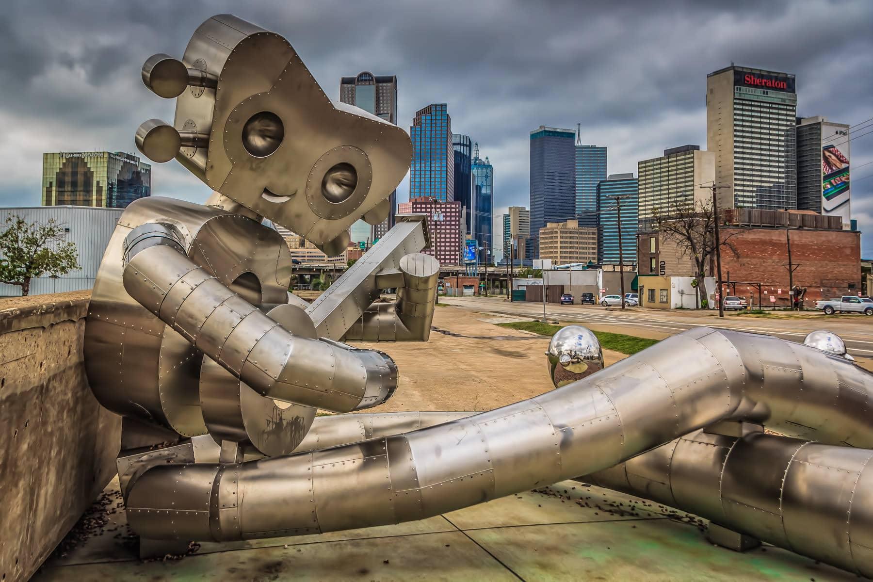 Dallas' Traveling Man sculpture—a landmark in the Deep Ellum neighborhood—against the city's downtown skyline.