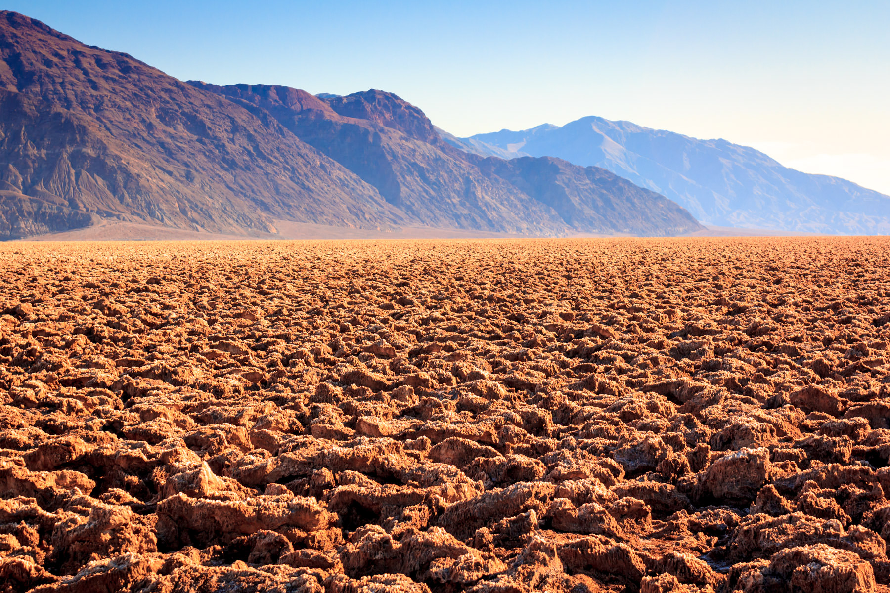 """The rugged landscape of California's Death Valley National Park's """"Devil's Golf Course""""; a large salt pan covered in large halite salt crystals deposited upon the evaporation of the prehistoric Lake Manly."""