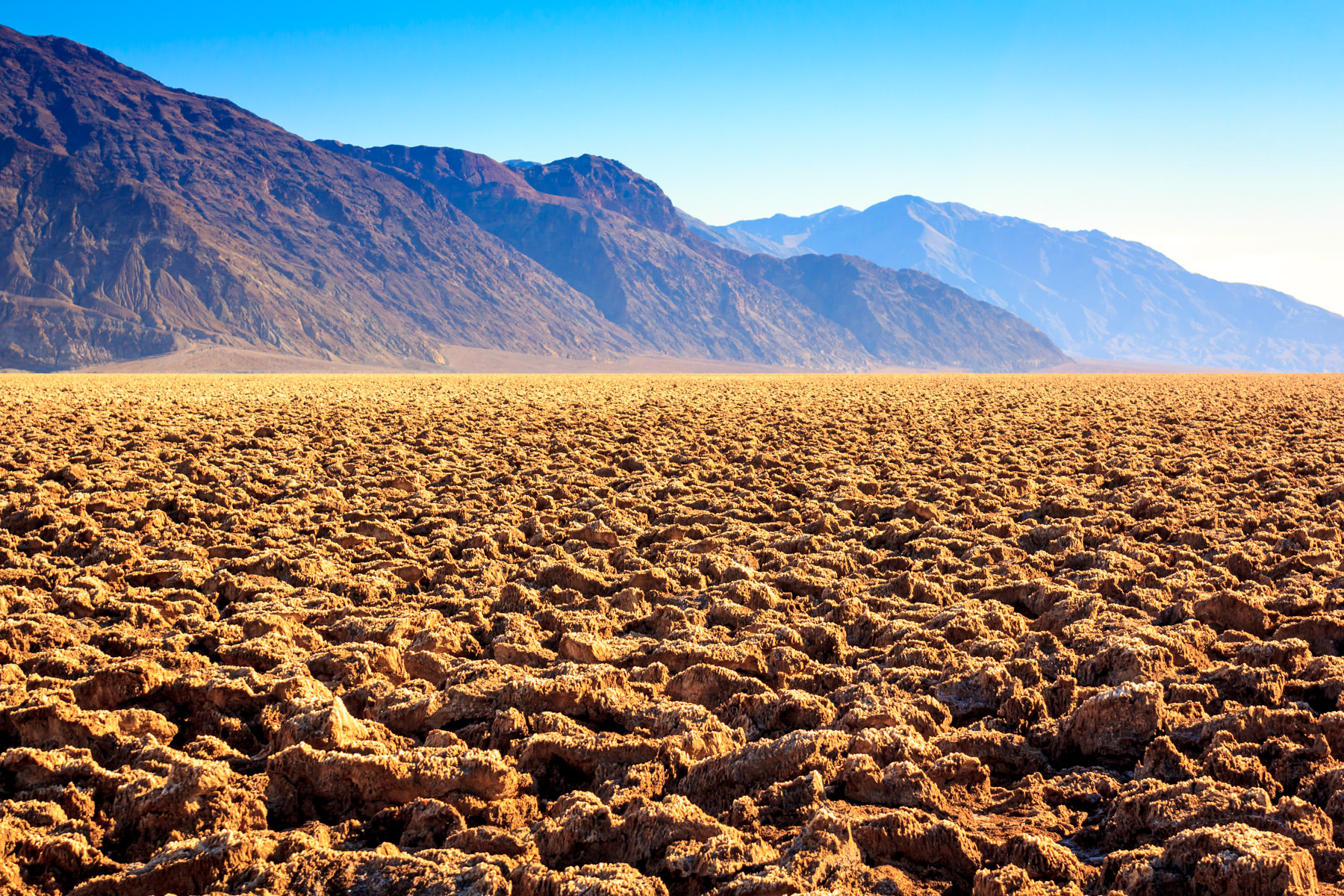 "The rugged landscape of California's Death Valley National Park's ""Devil's Golf Course""; a large salt pan covered in large halite salt crystals deposited upon the evaporation of the prehistoric Lake Manly."