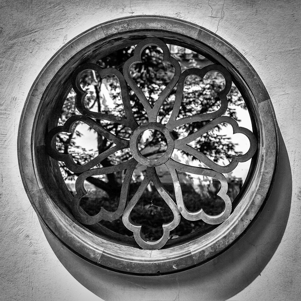 An ornate window between two gardens at Montréal's Jardin Botanique.