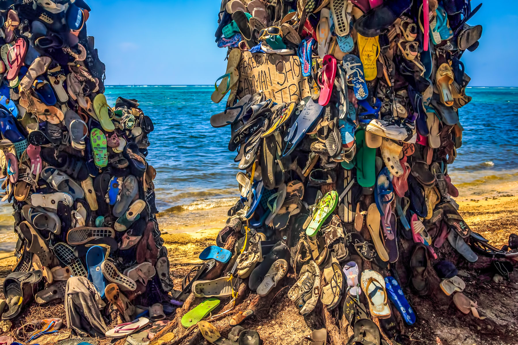 "Known to the residents of and visitors to Grand Cayman as the ""Cayman Shoe Tree"" (although it's actually two trees), this local landmark is a depository for orphaned shoes found on the beaches of the island, as well as a reminder not to litter."