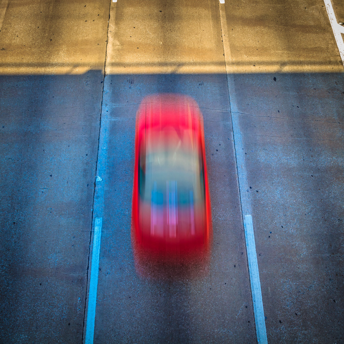 A car speeds along Dallas' Woodall Rogers Freeway in this shot from a bridge over the roadway.