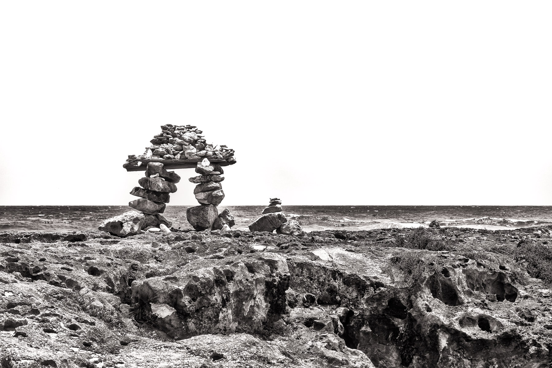 An inukshuk—a stone landmark traditionally constructed by the Inuit of far north Canada, Alaska and Greenland—inexplicably found on a rocky beach on Cozumel, Mexico.